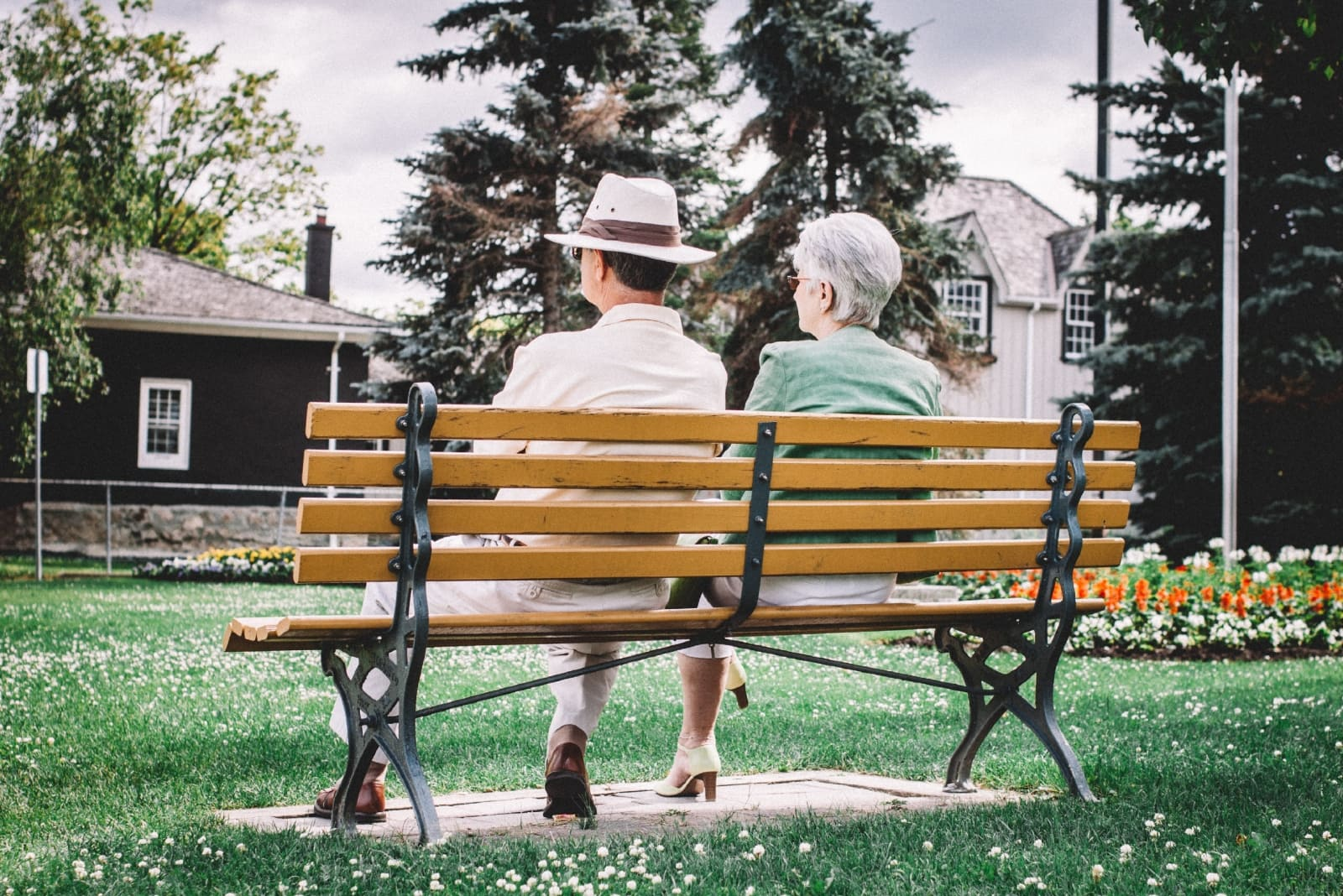 man with hat and woman sitting on bench
