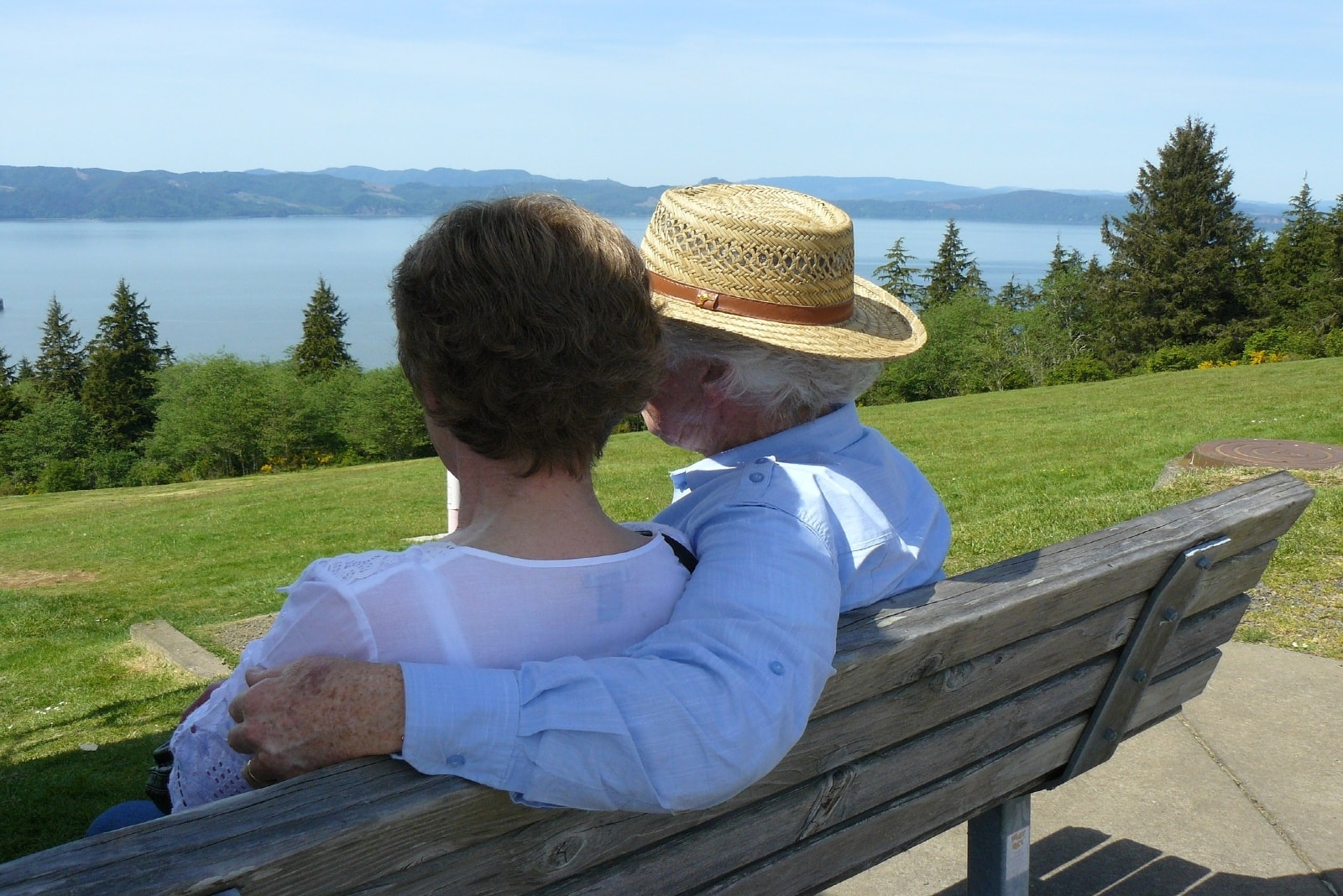 man with hat and woman hugging while sitting on bench