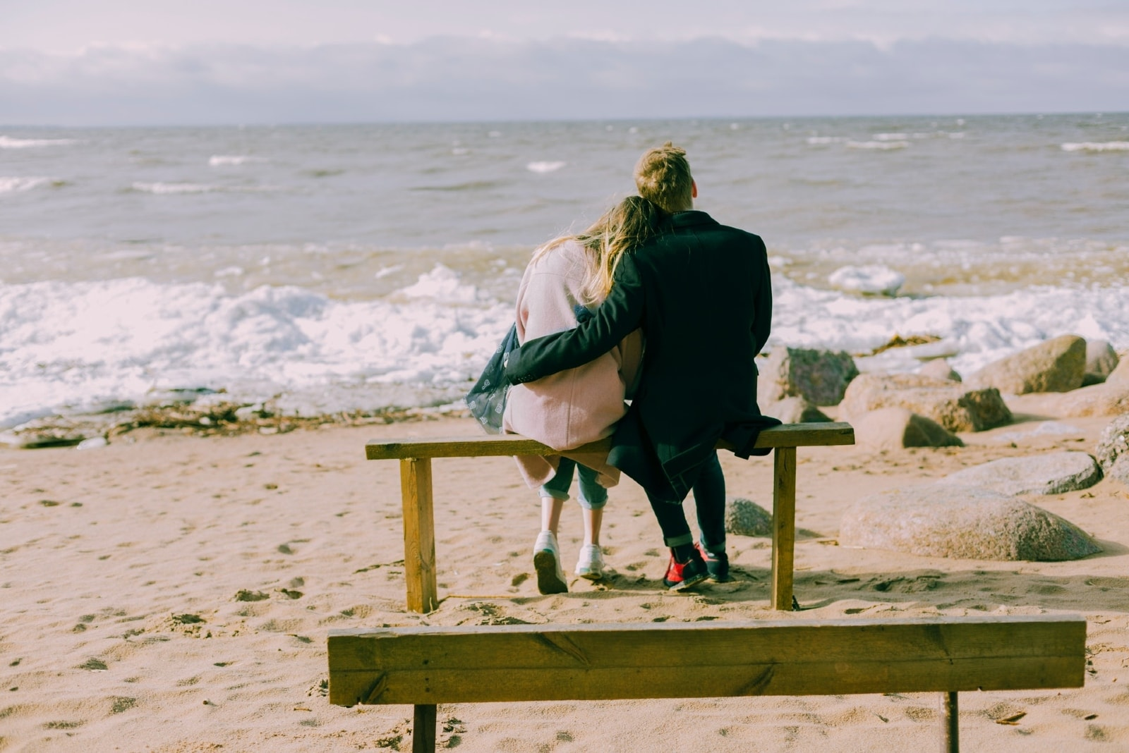 man and woman sitting on bench while looking at sea