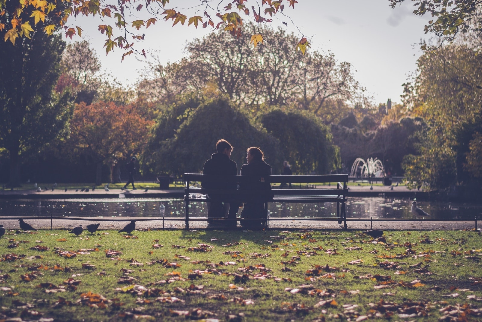 man and woman sitting on bench near water