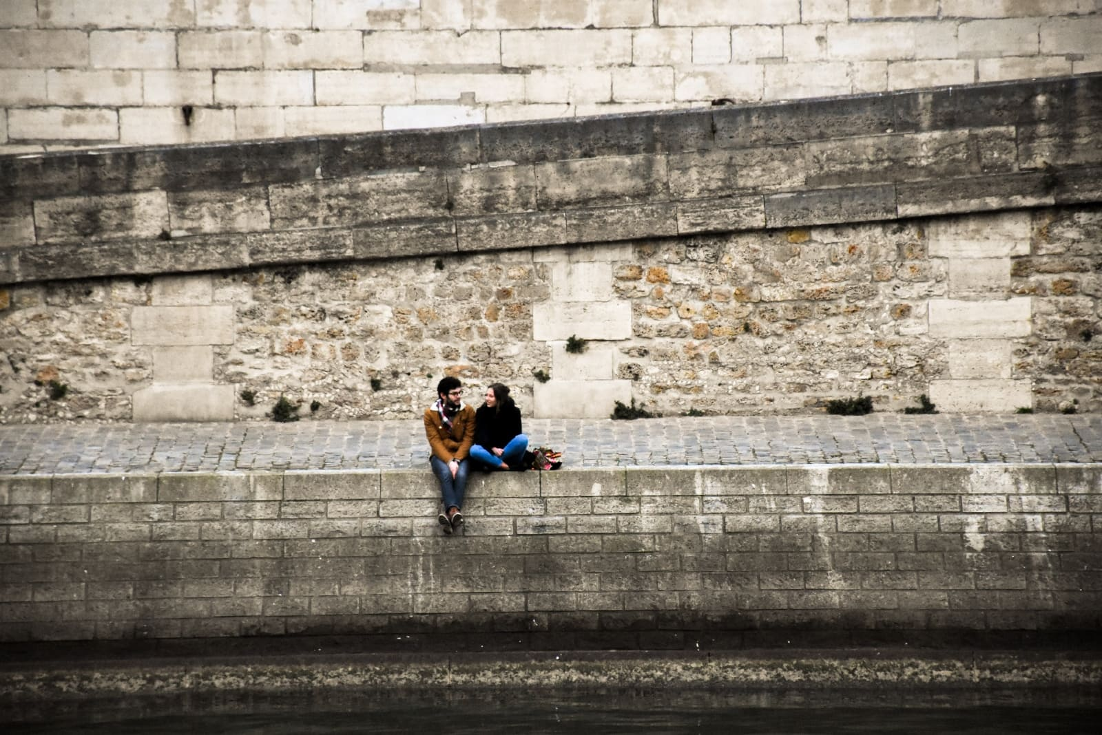man and woman talking while sitting on concrete surface