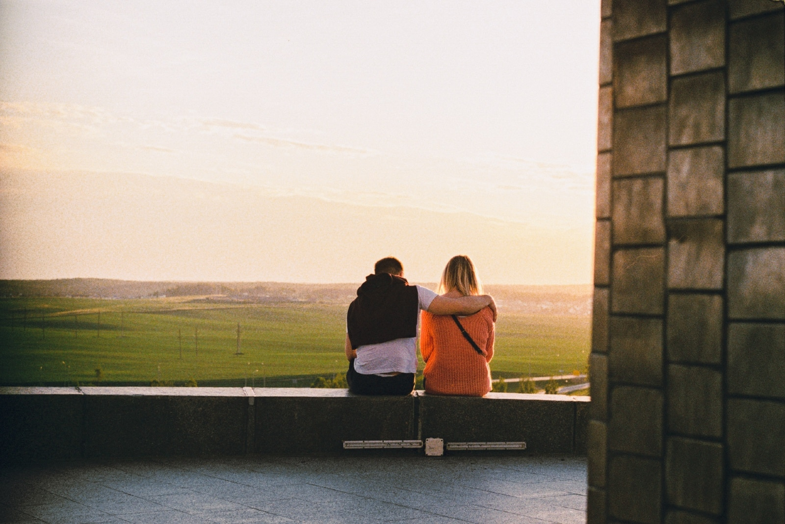 man hugging woman while sitting on concrete surface outdoor