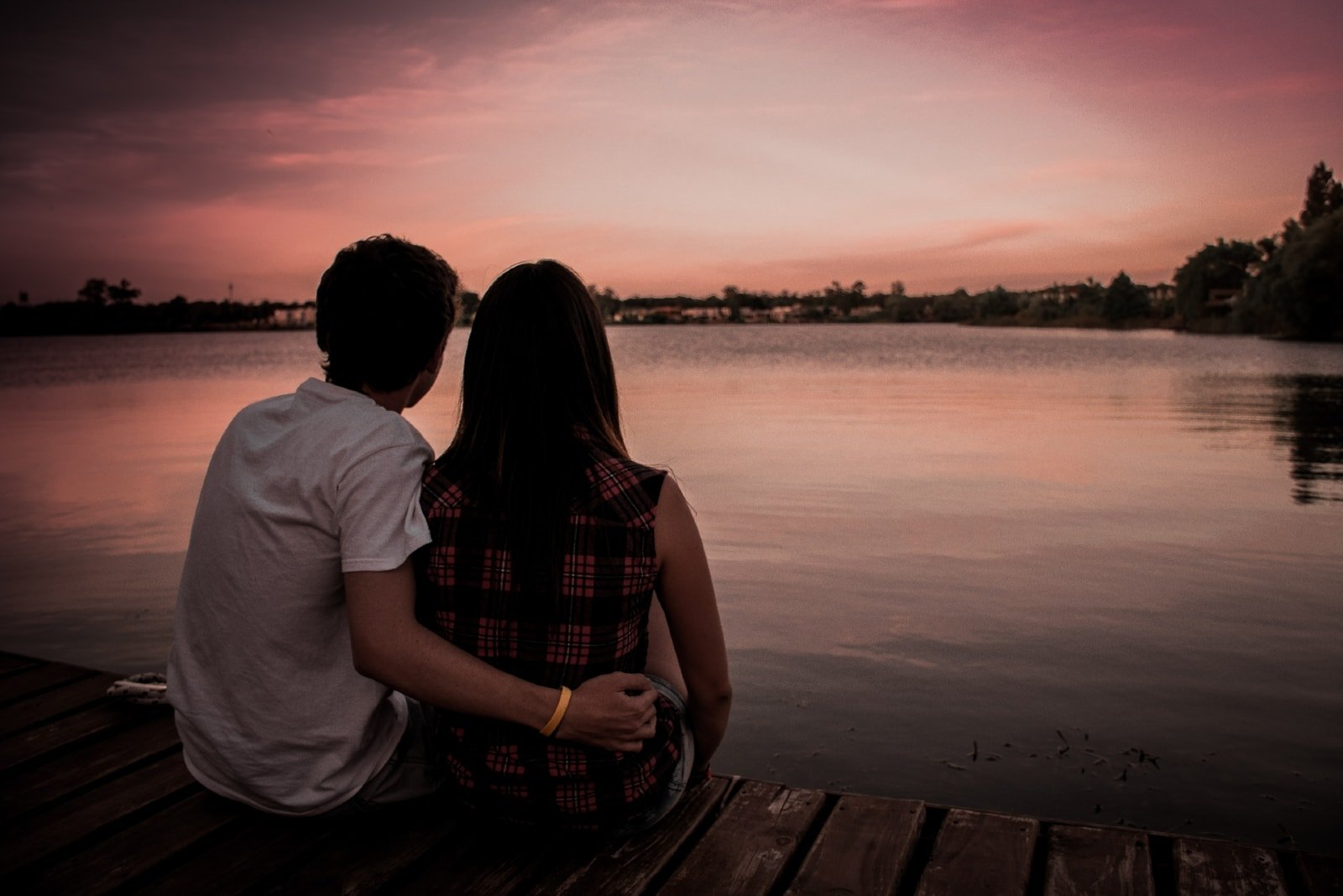 man and woman sitting on dock during sunset