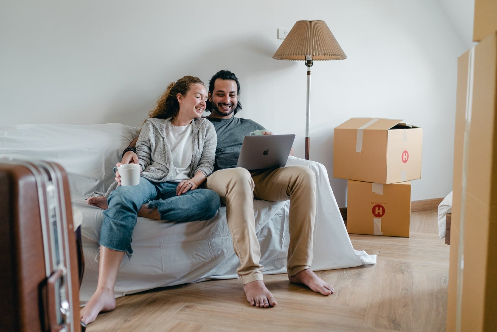 man and woman looking at laptop while sitting on sofa