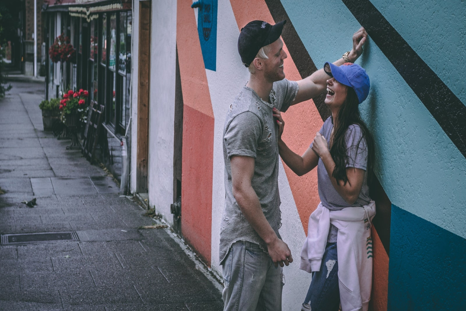 man and woman making eye contact while standing near wall