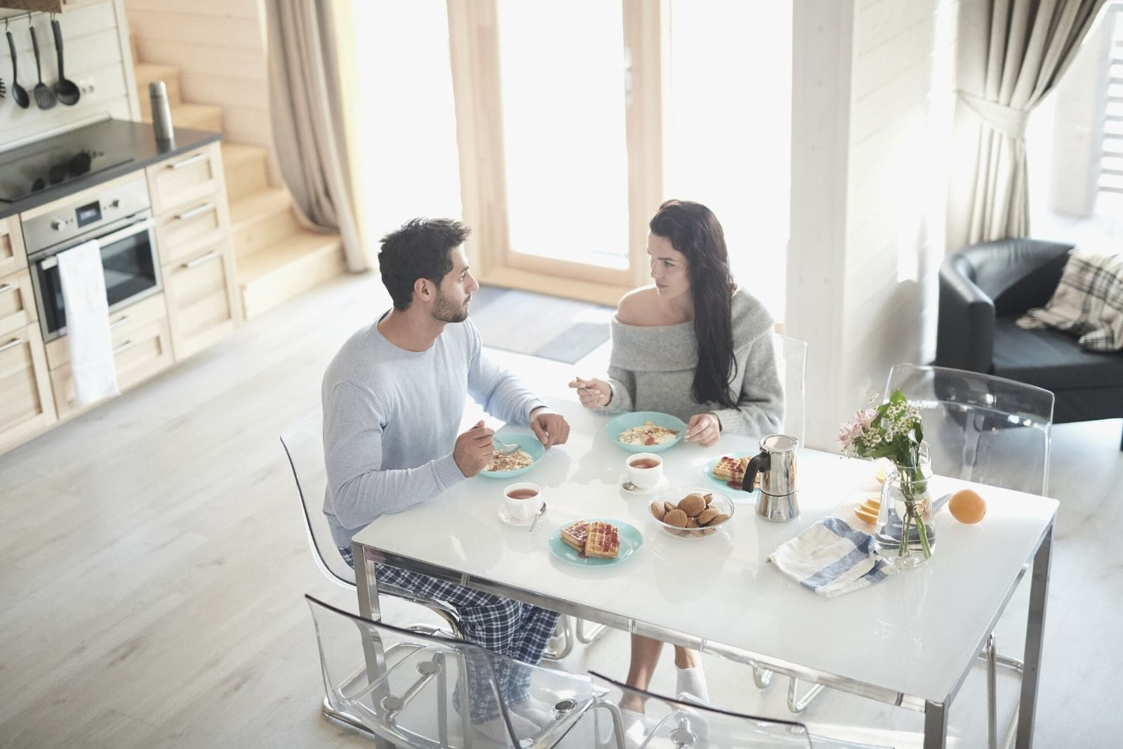 couple talking seriously during breakfast at the table at high angle