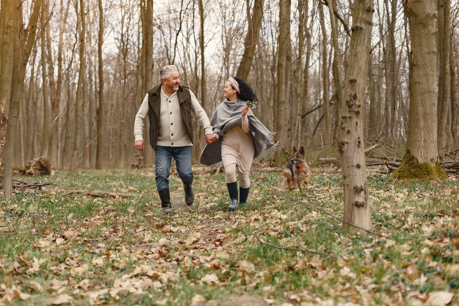 man and woman walking in forest with dog