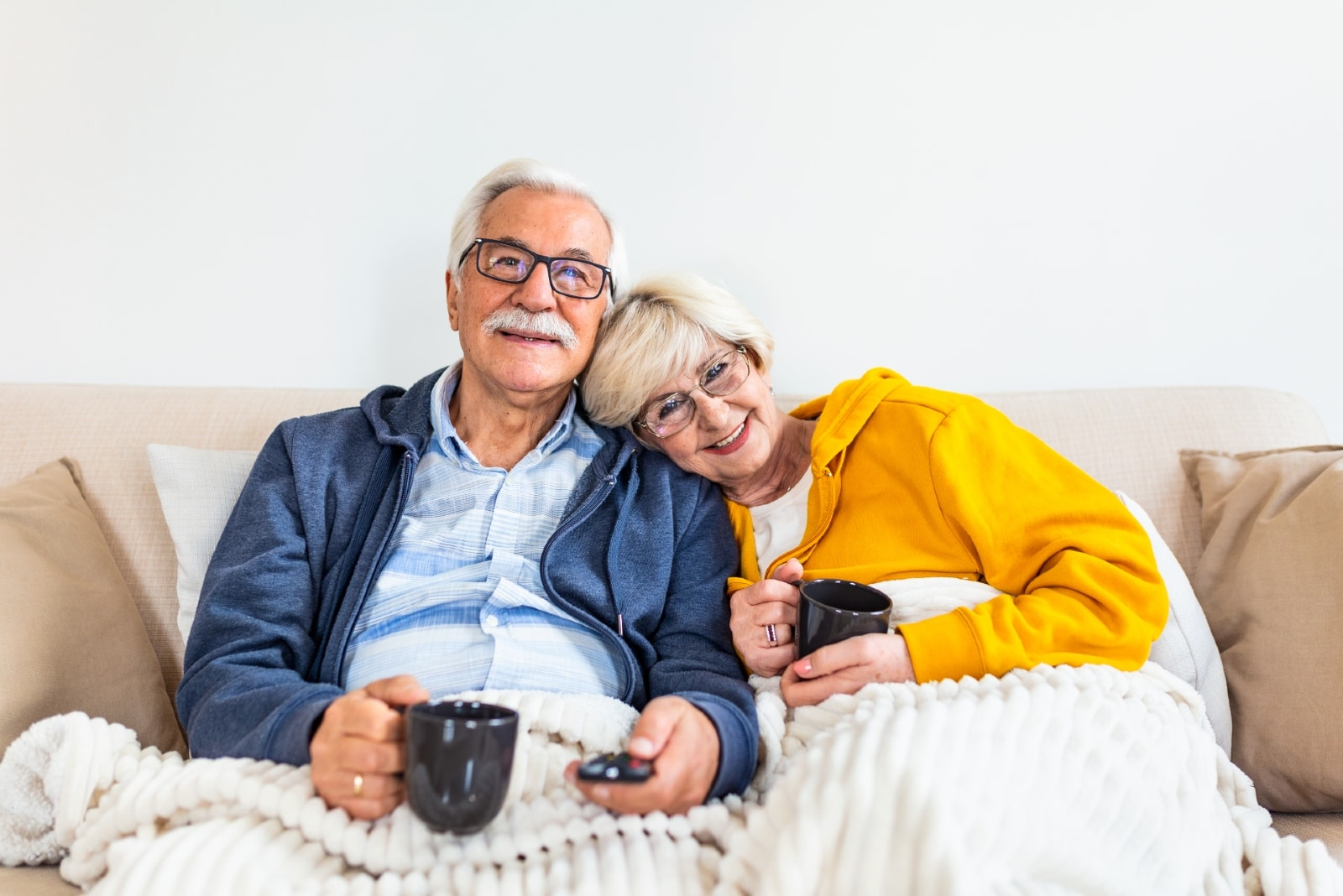 man and woman watching tv while holding black mugs