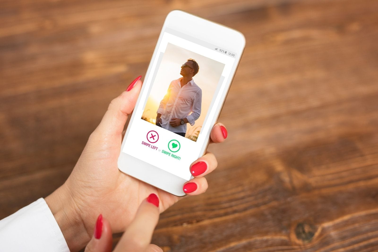 cropped hand of a woman holding a smartphone with a picture of a man in a dating app