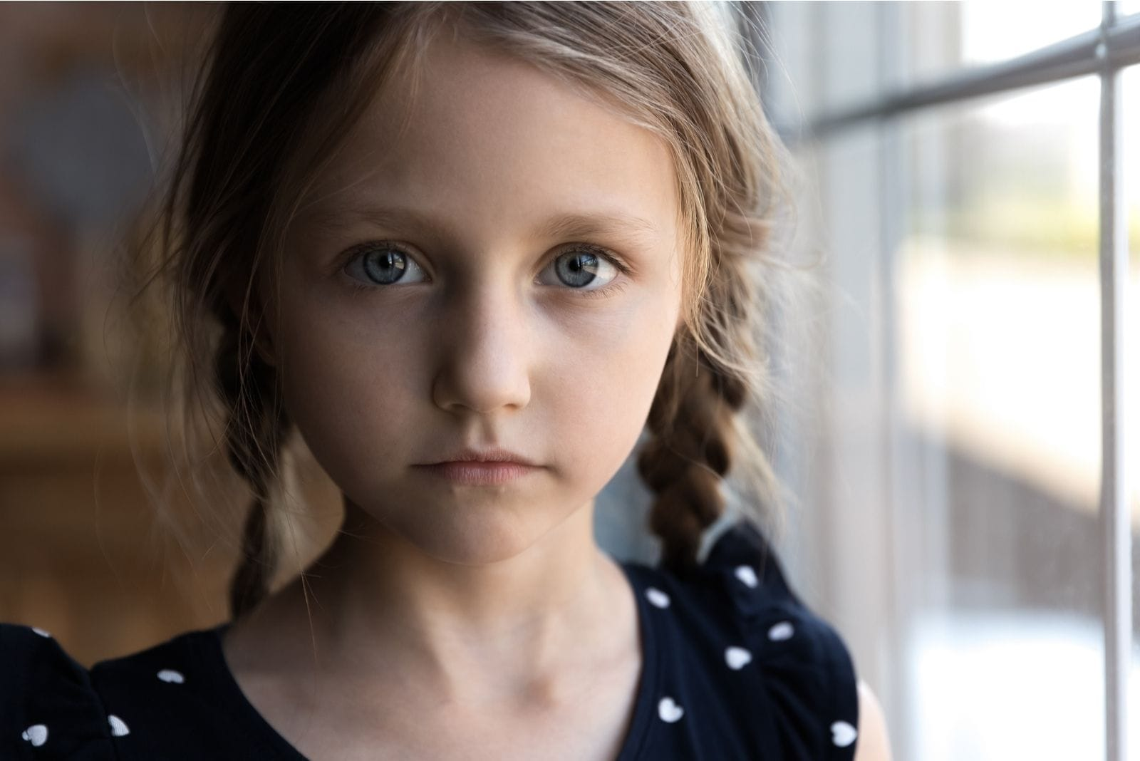 cropped image of a sad child looking at the camera standing beside the windows