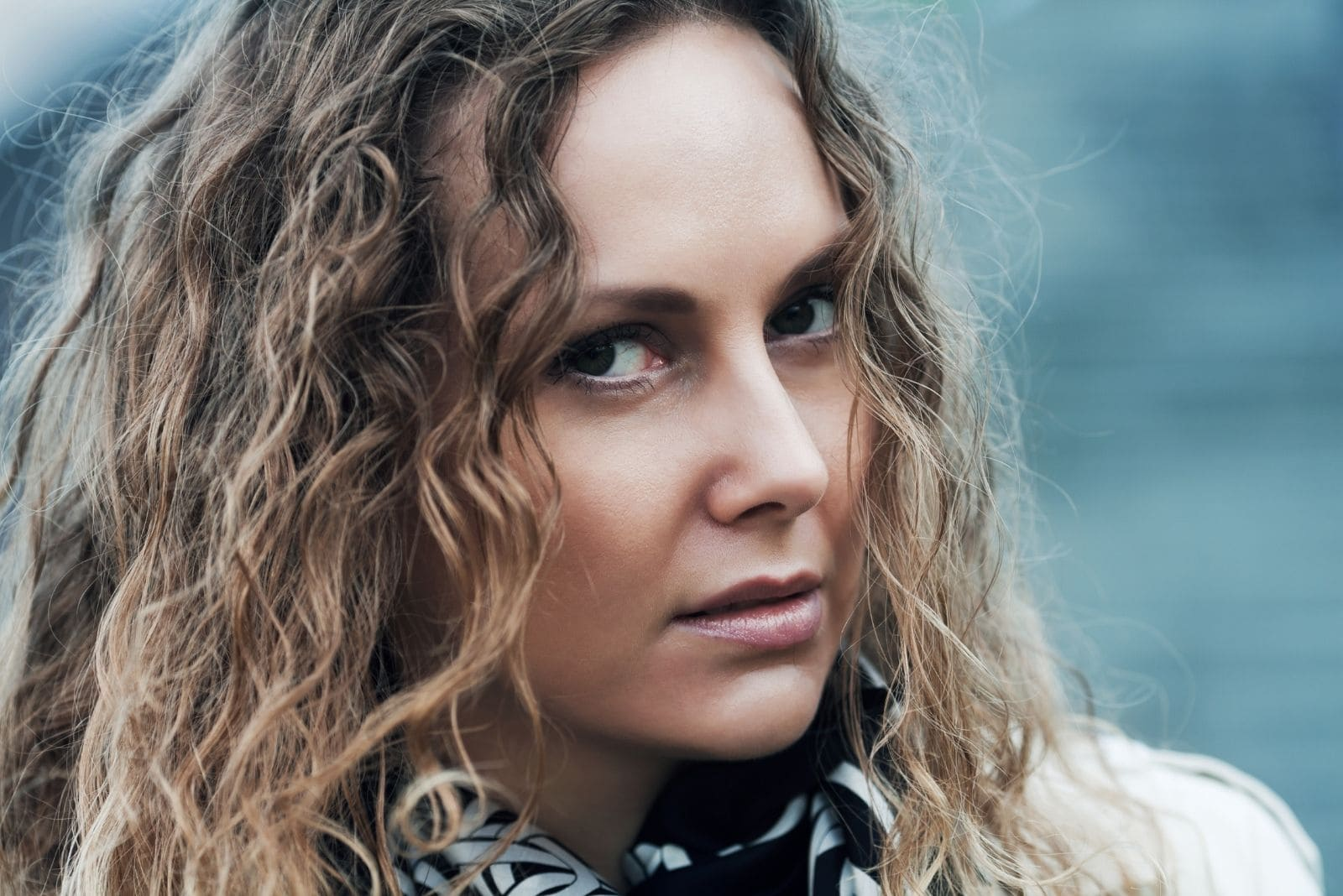 curly blonde haired woman looking at the camera with deep thoughts