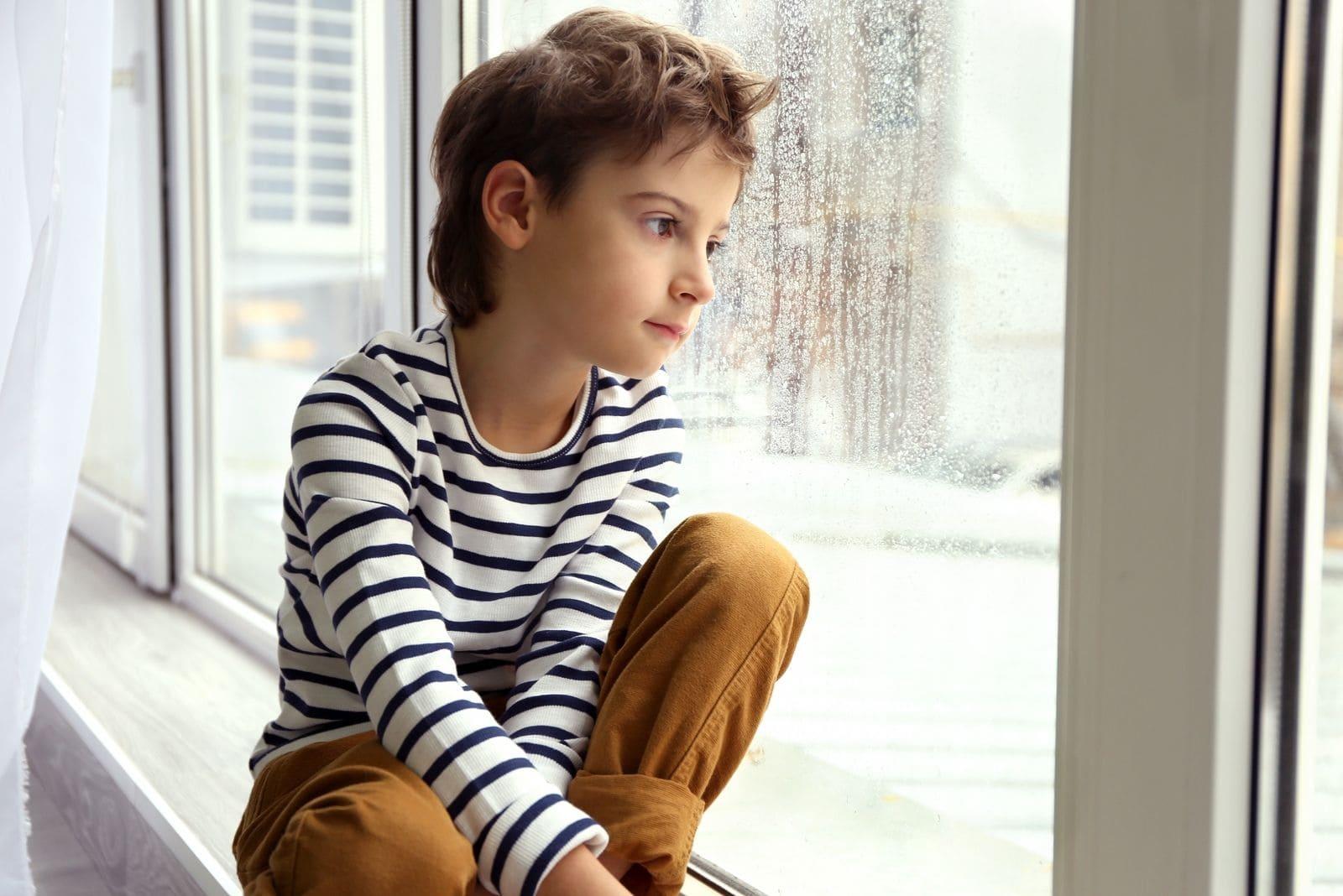 cute little boy sitting by the window sill looking outside