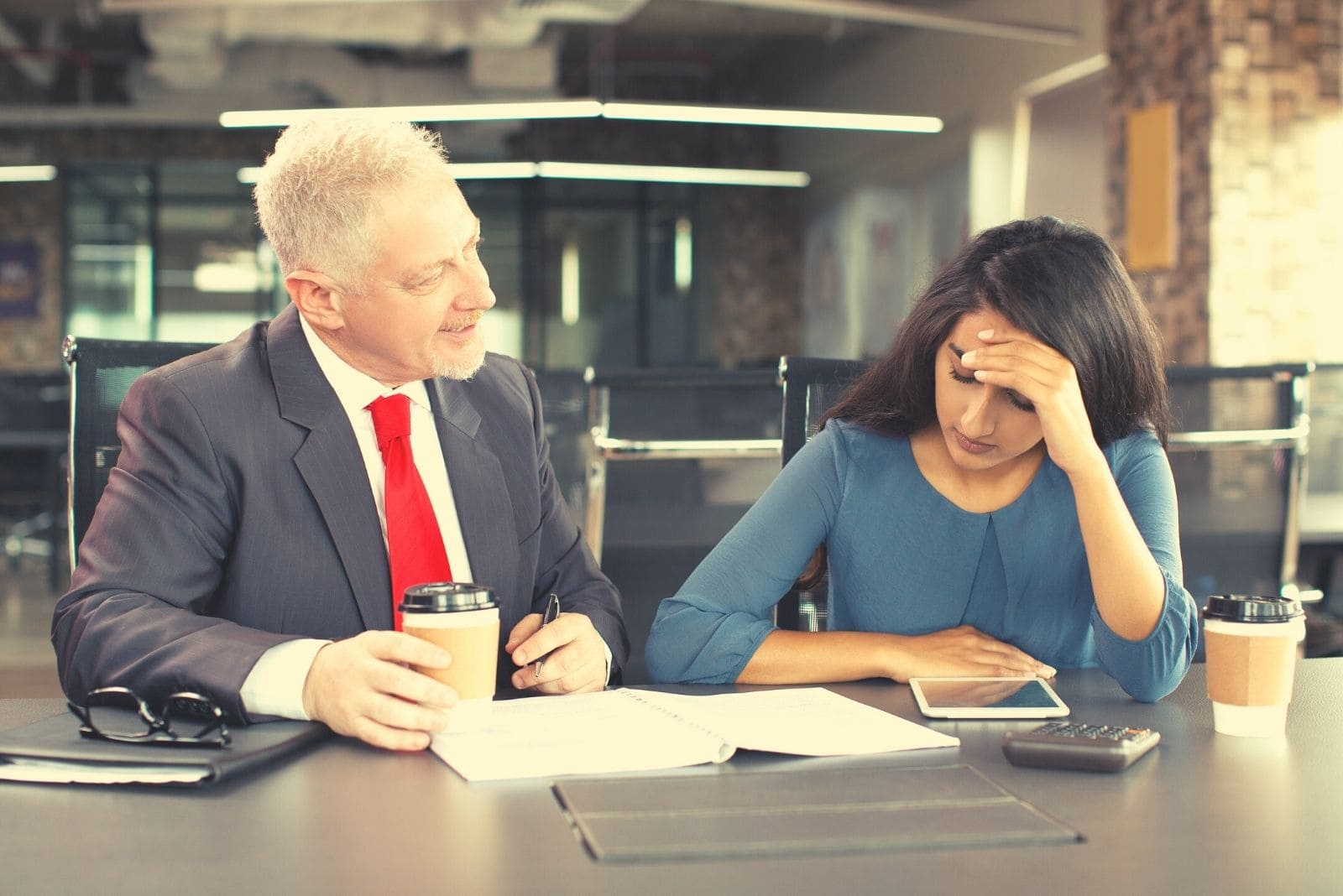 displeased leader blaming young businesswoman while having coffee and sitting by the table