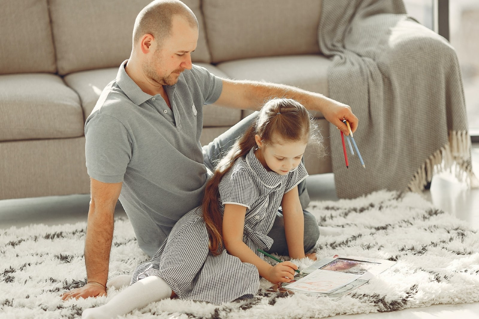 father holding colored pencils while sitting near daughter on carpet