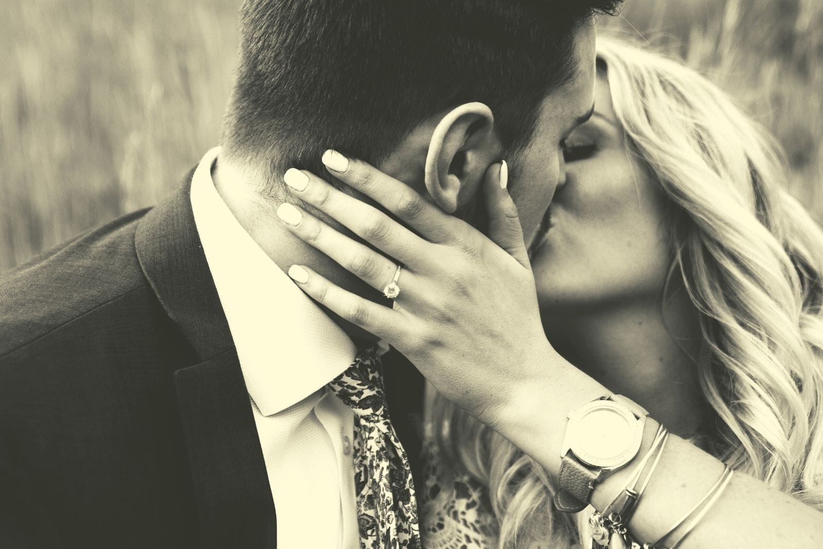 grayscale theme of kissing couple wearing formal wear outdoors