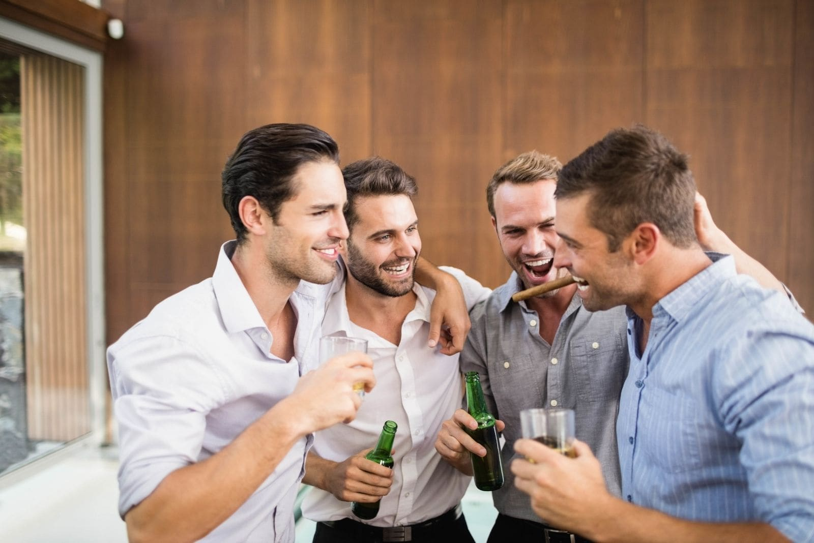 group of young men enjoying drinking inside a room in a building