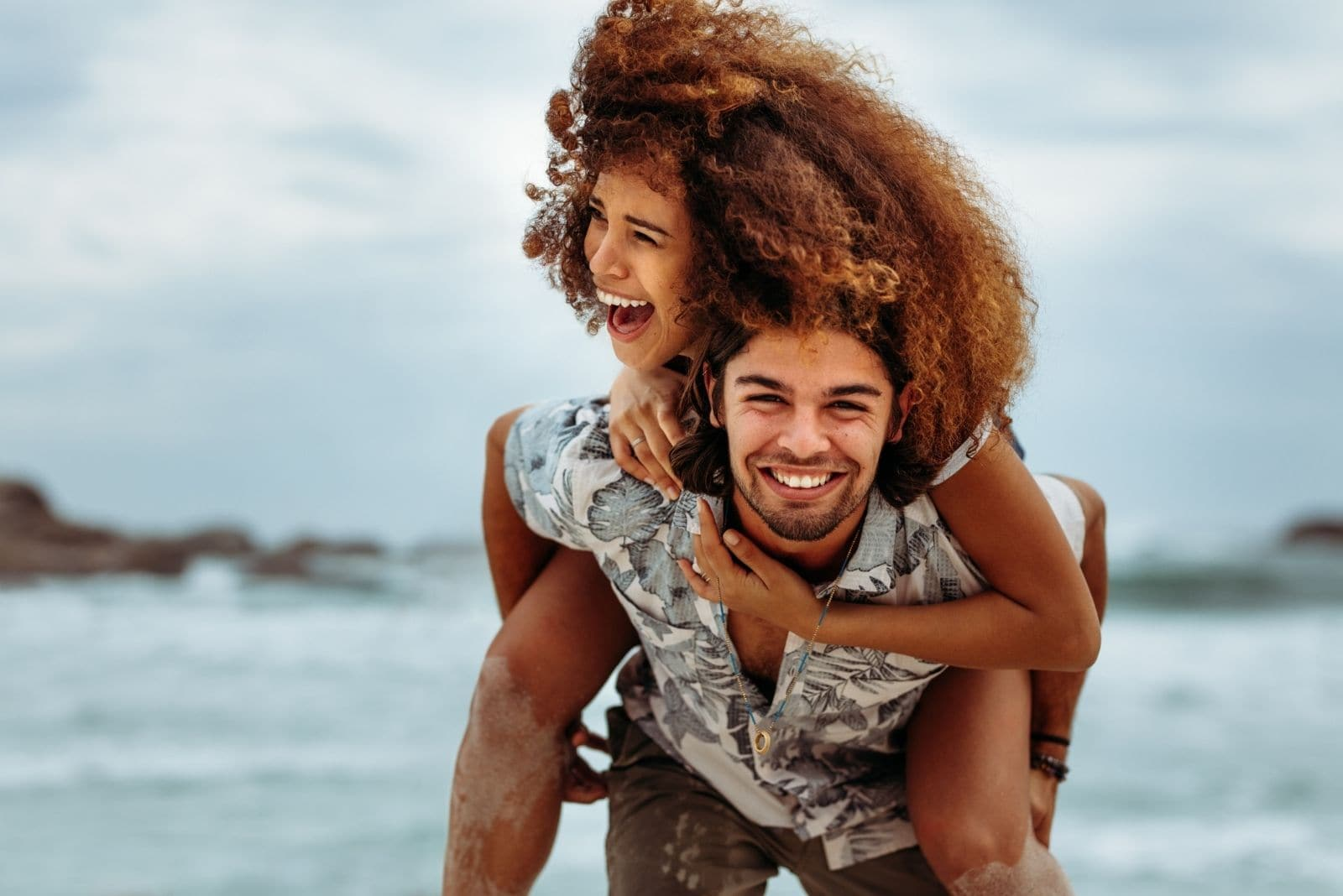 happy couple piggybacking and laughing in the beach