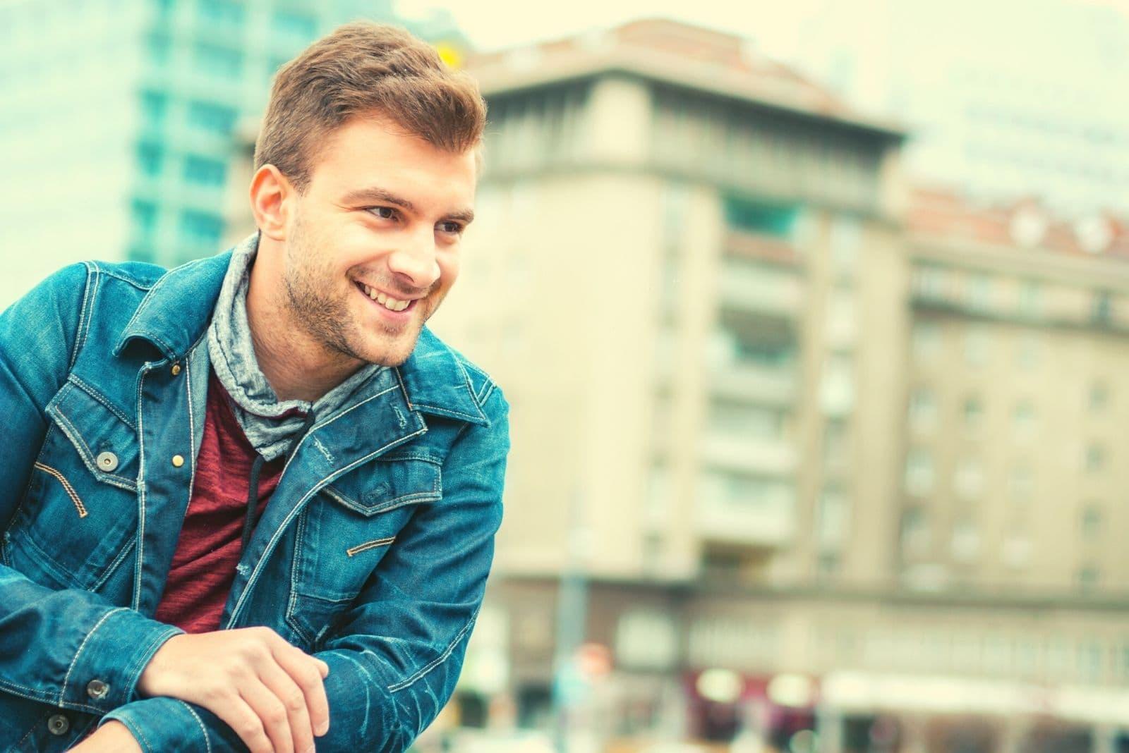 happy man smiling outdoors wearing denim jacket