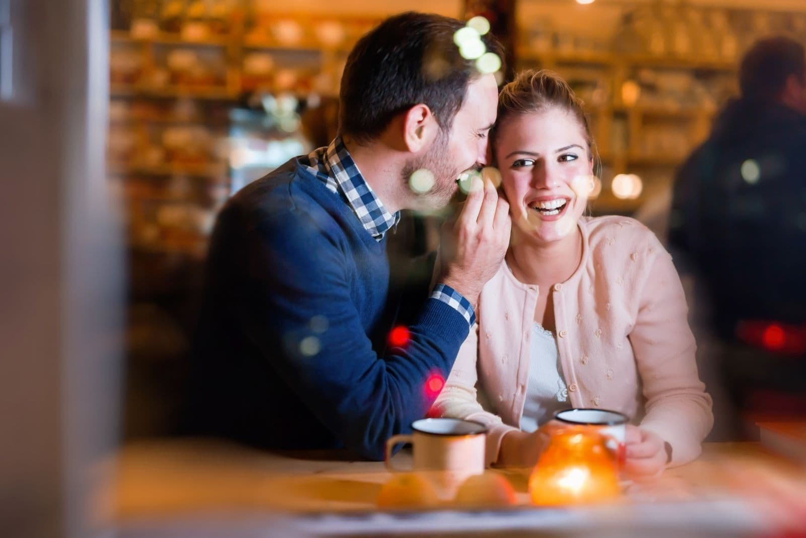 happy man whispering on the woman's ear while dating in a restaurant