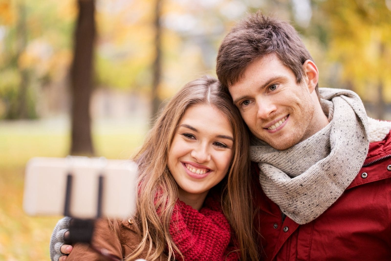 happy smiling couple taking a picture with smartphone and selfie stick during autumn season