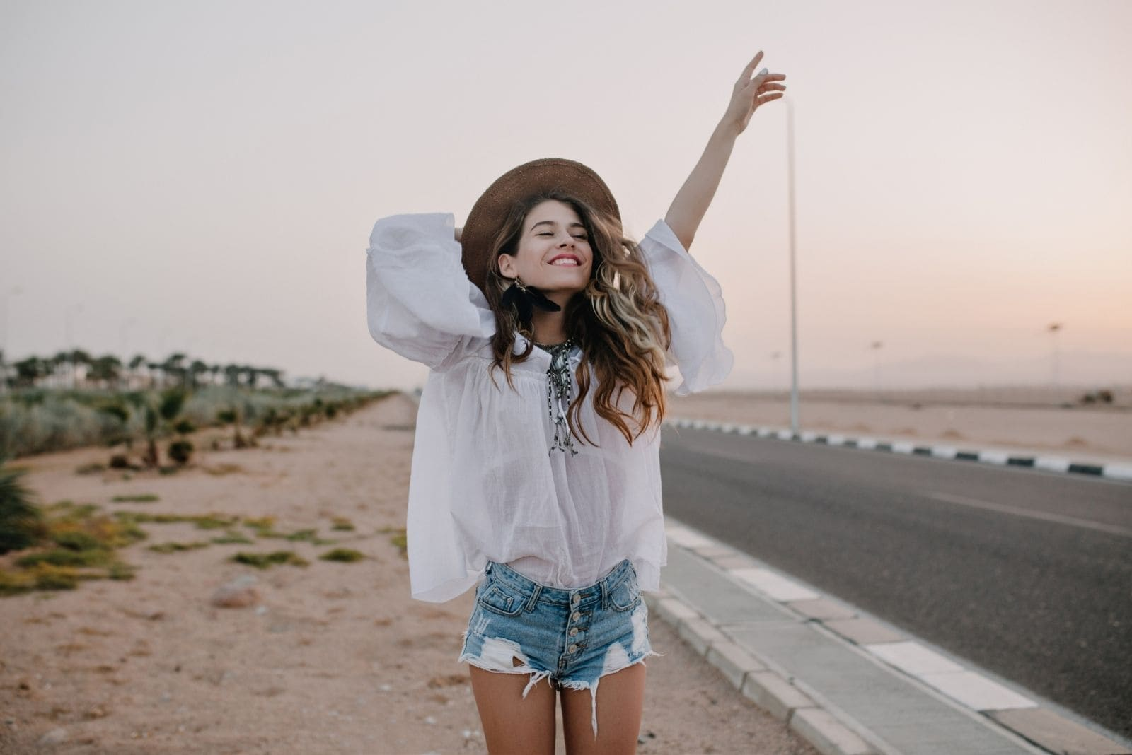 happy woman stands near the street along the highways holding her hat and raising one arm