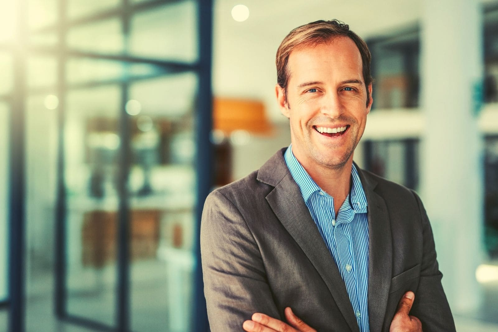 happy young businessman standing in the modern office and smiling