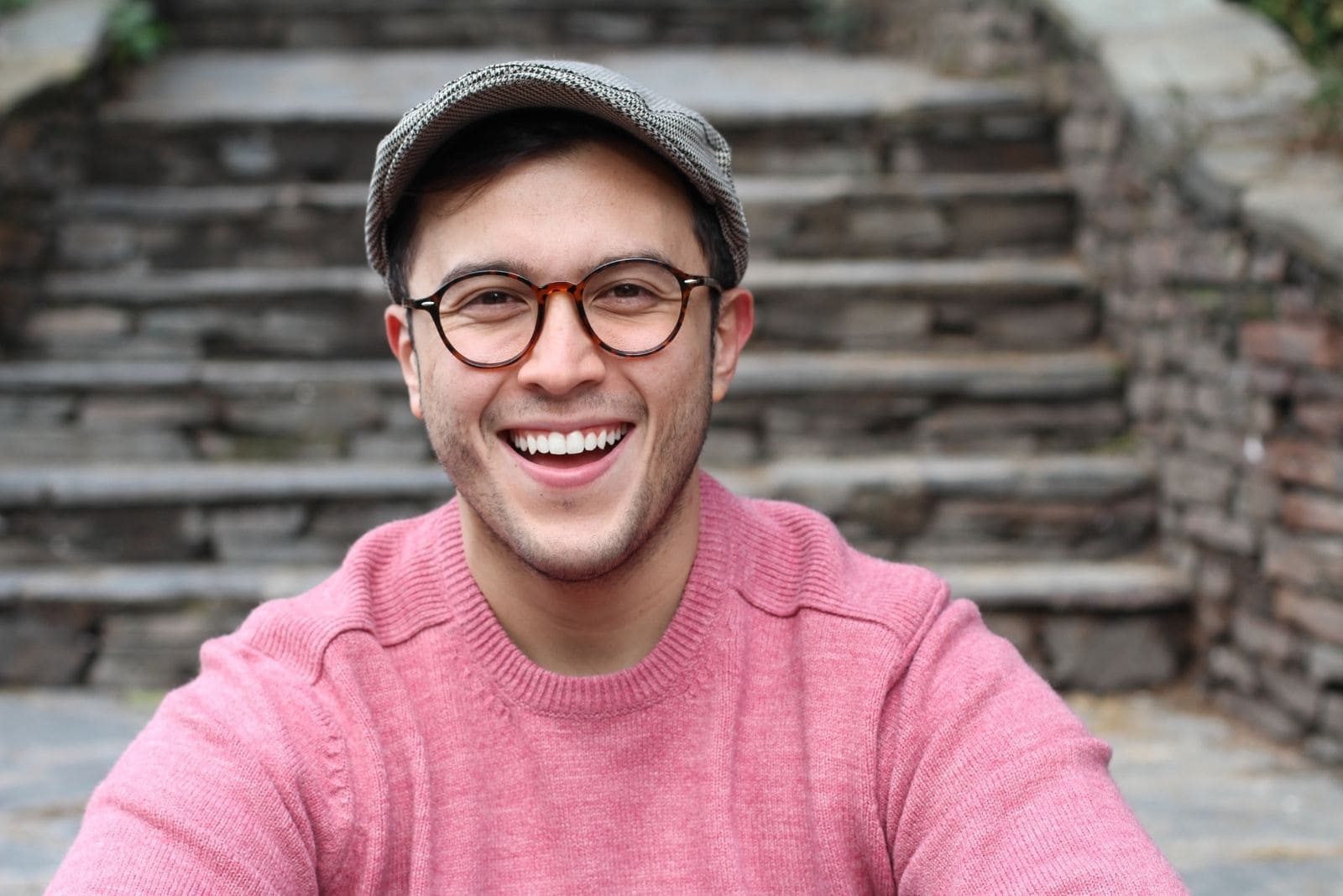 hip man smiling wearing hat and eyeglasses sitting near the cement stairs