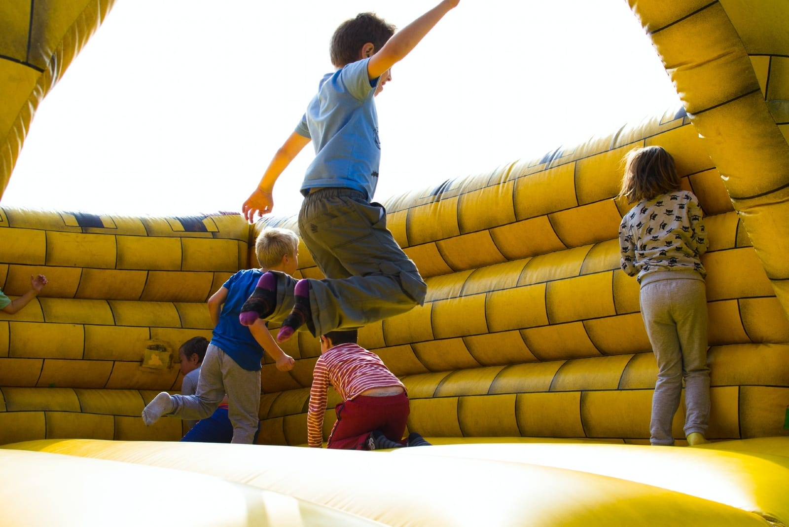 kids playing in yellow inflatable castle