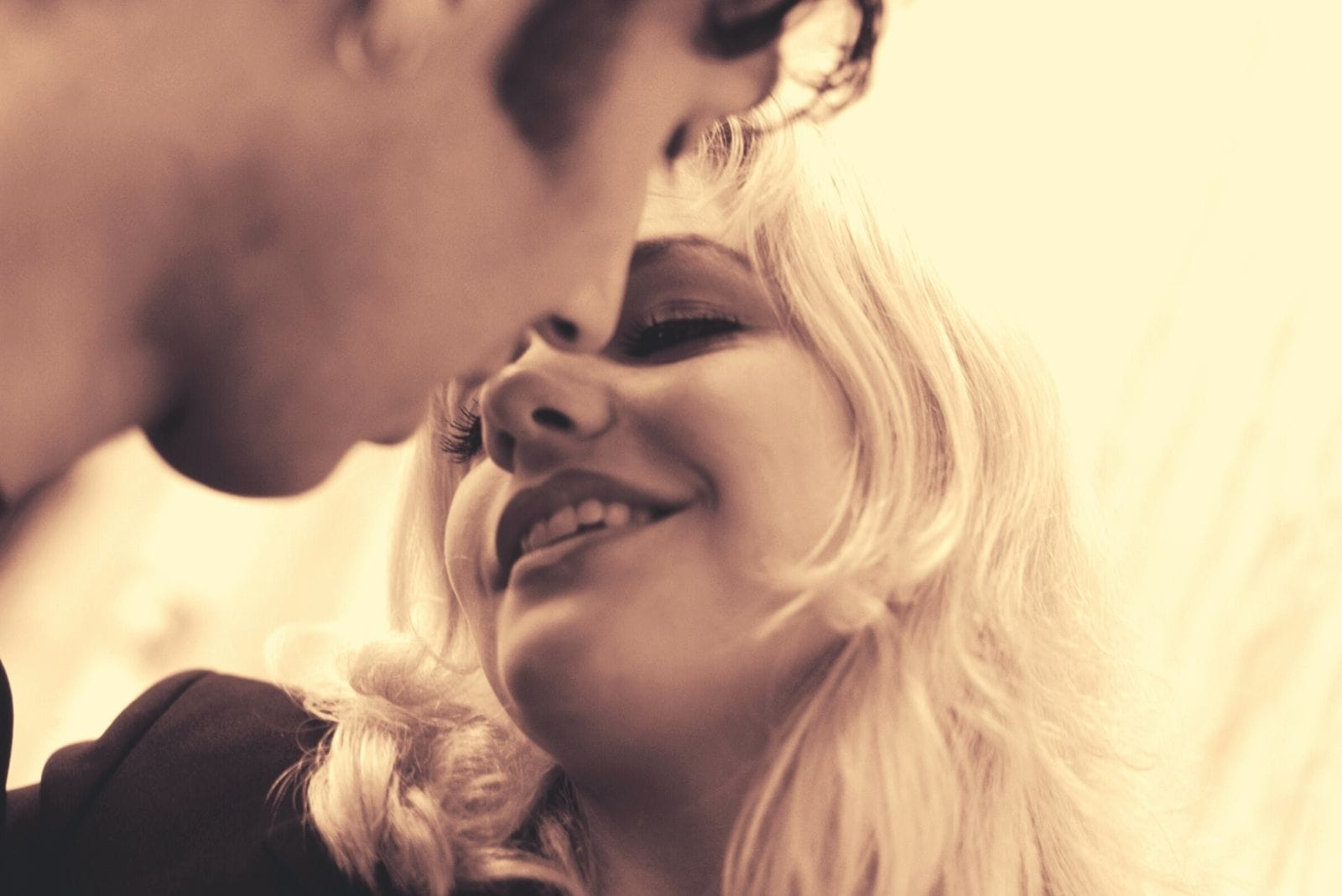 kissing couple smiling in their 20-30s with photography in grayscale theme their