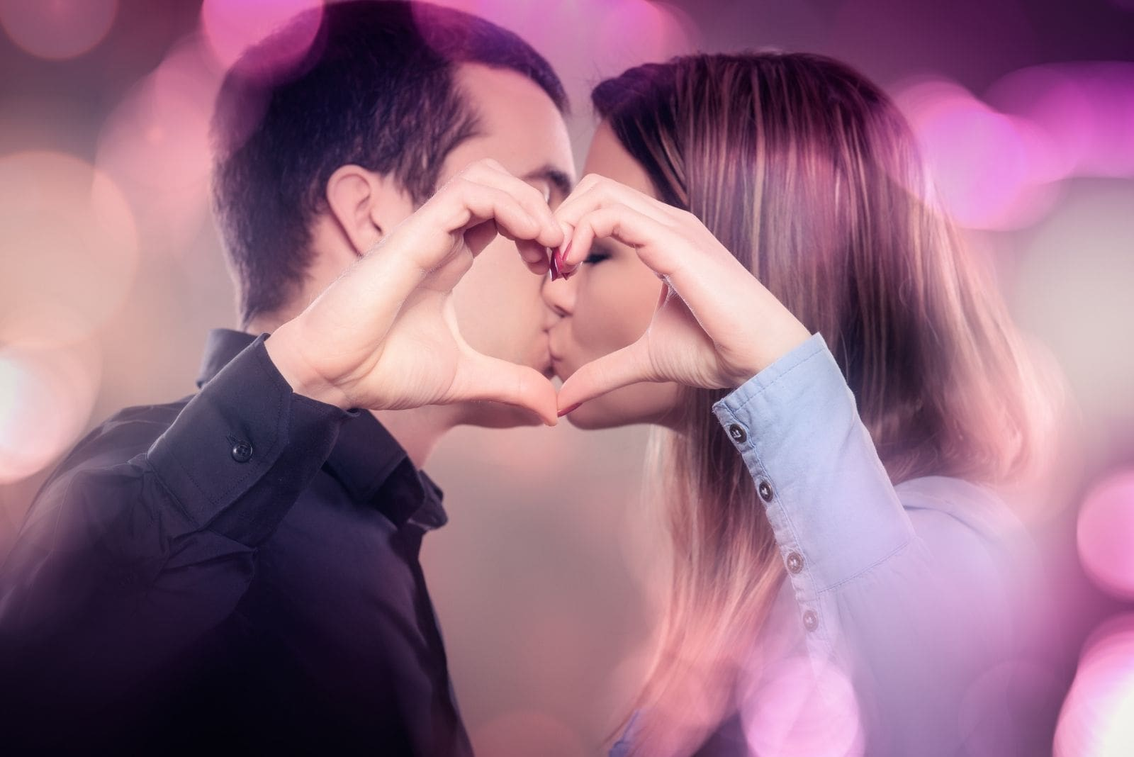 kissing young couple making a heart shape with bubble of colors around