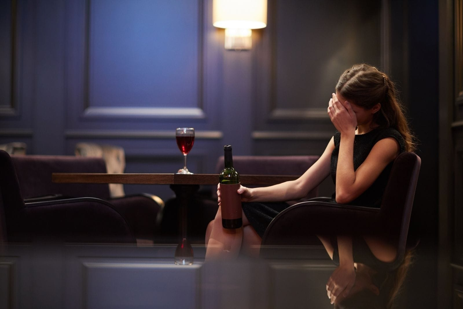 lonely young woman sad with a bottle of red wine in a luxurious hotel