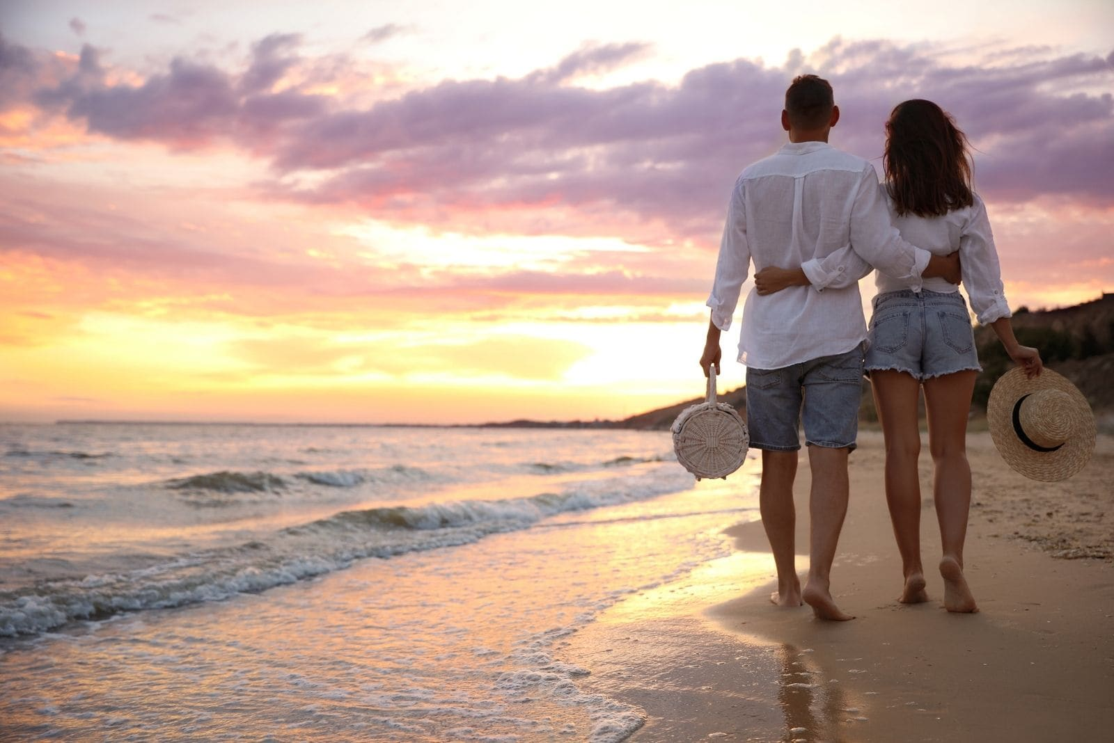 lovely couple walking on the beach side by side during sunset