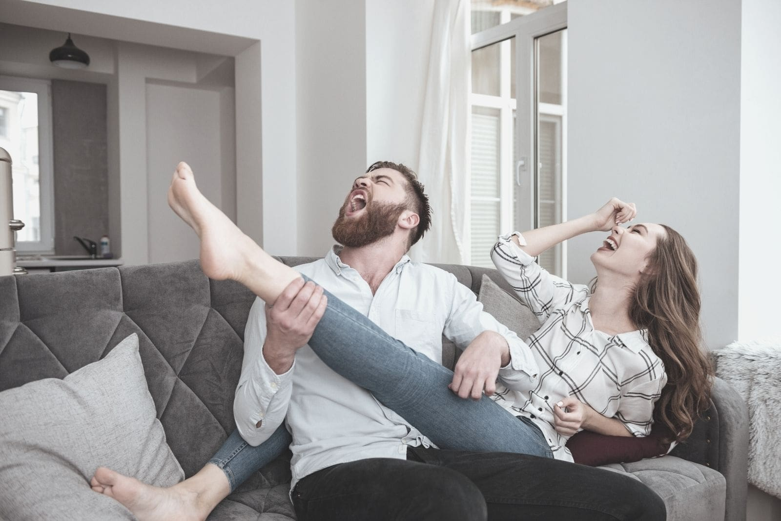 lovely funny couple sitting in sofa with the man imagining the woman's leg is a guitar