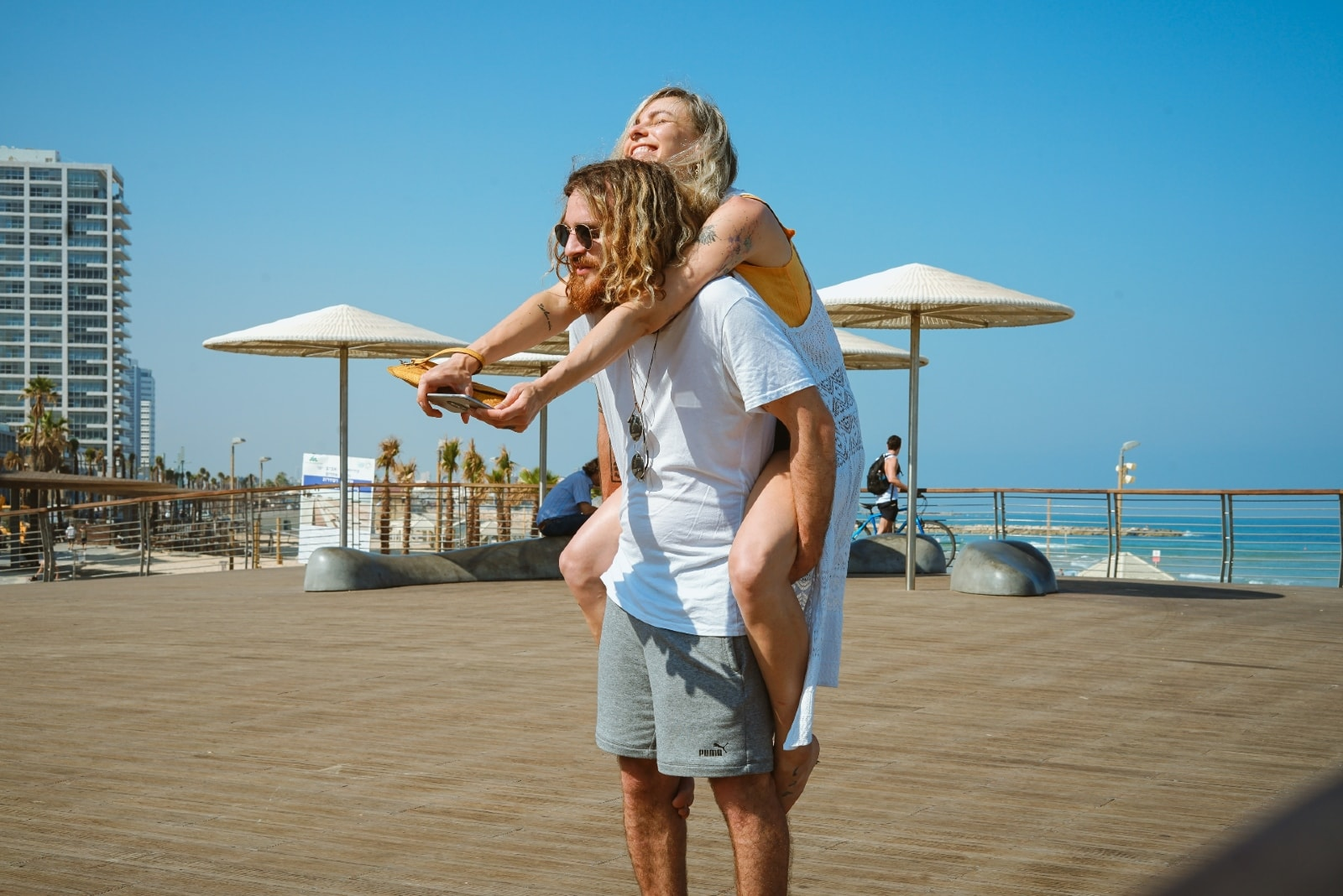 man in white t-shirt carrying woman outdoor