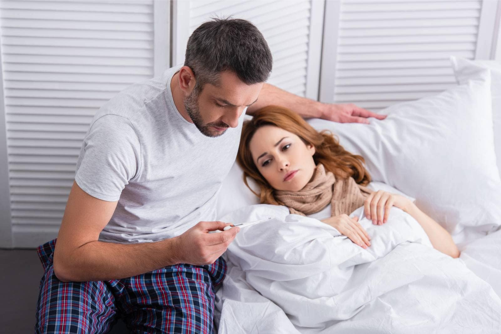 man checking on temperature on the thermometer of a sick woman lying on bed besiide him