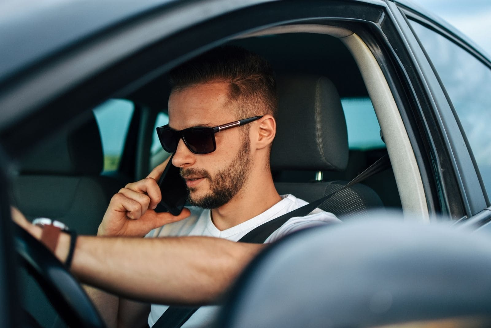 man driving a car answering the phone wearing sunglasses