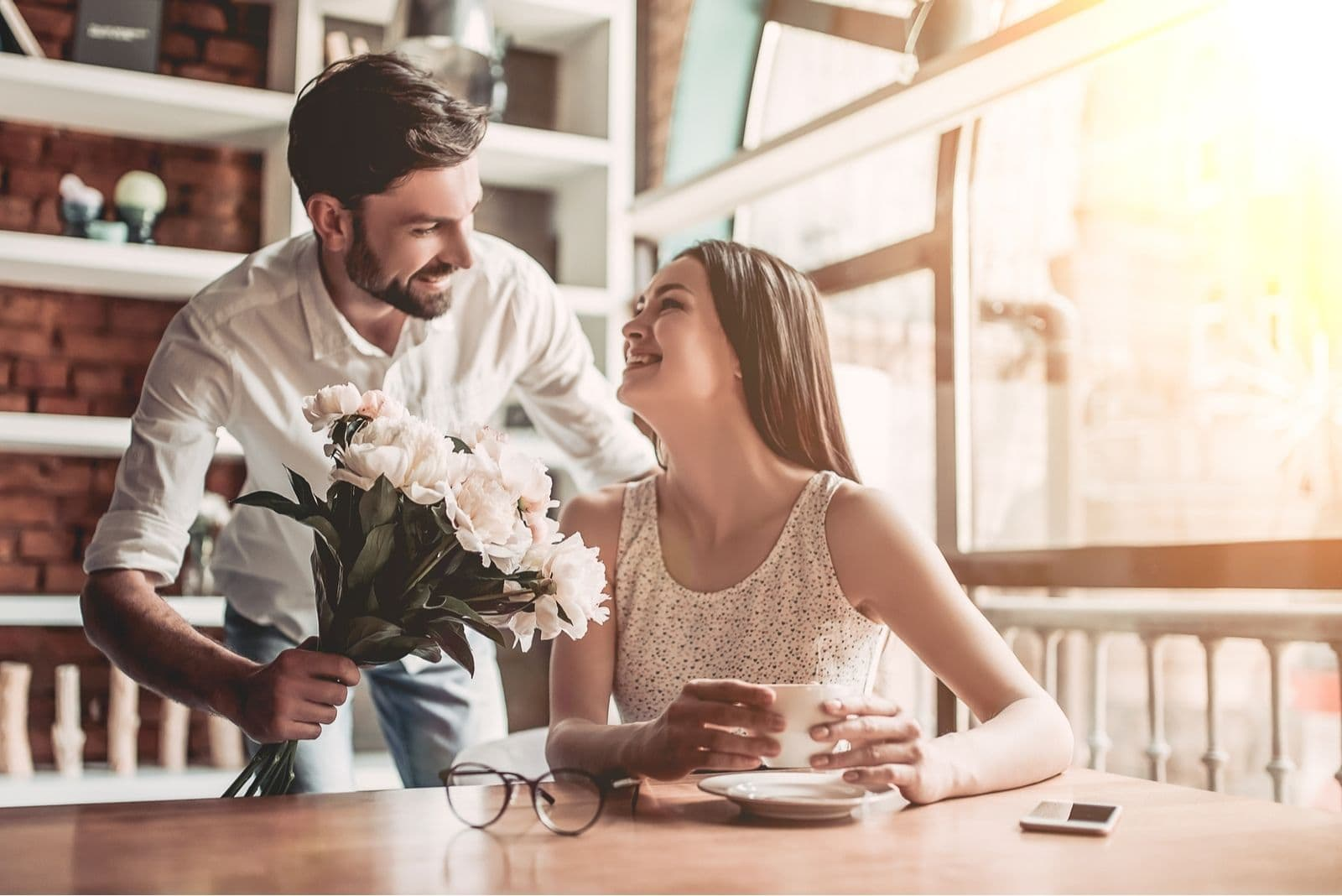 man giving flower to a beautiful woman sitting inside the cafe lloking surprised