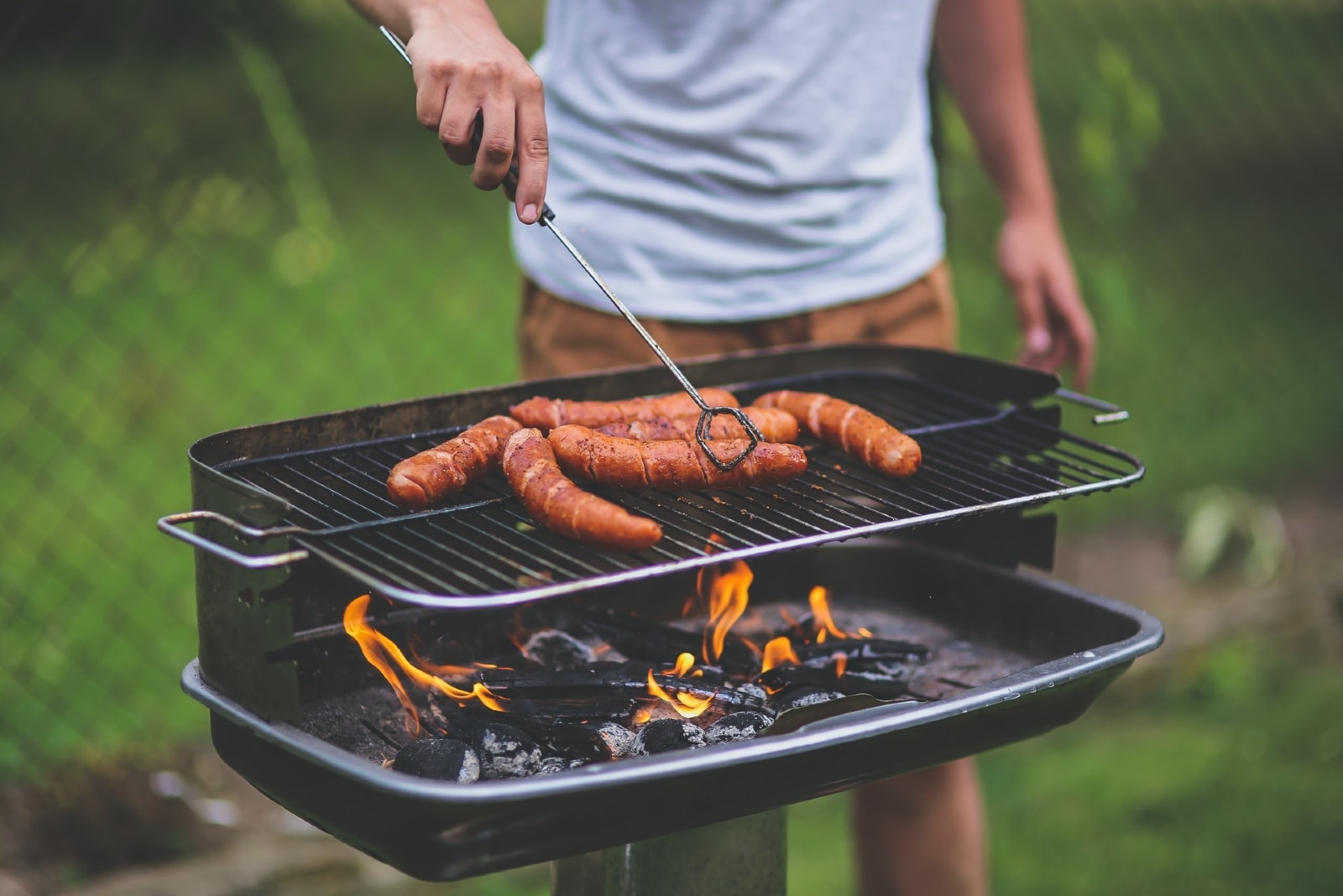 man grilling sausages on barbecue