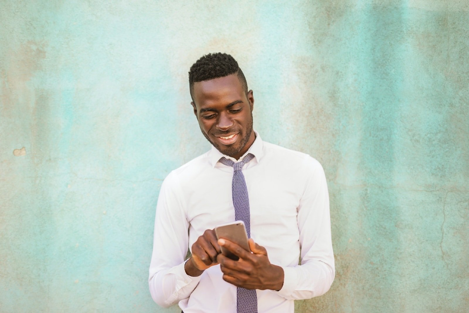 happy man in white shirt holding smartphone near wall