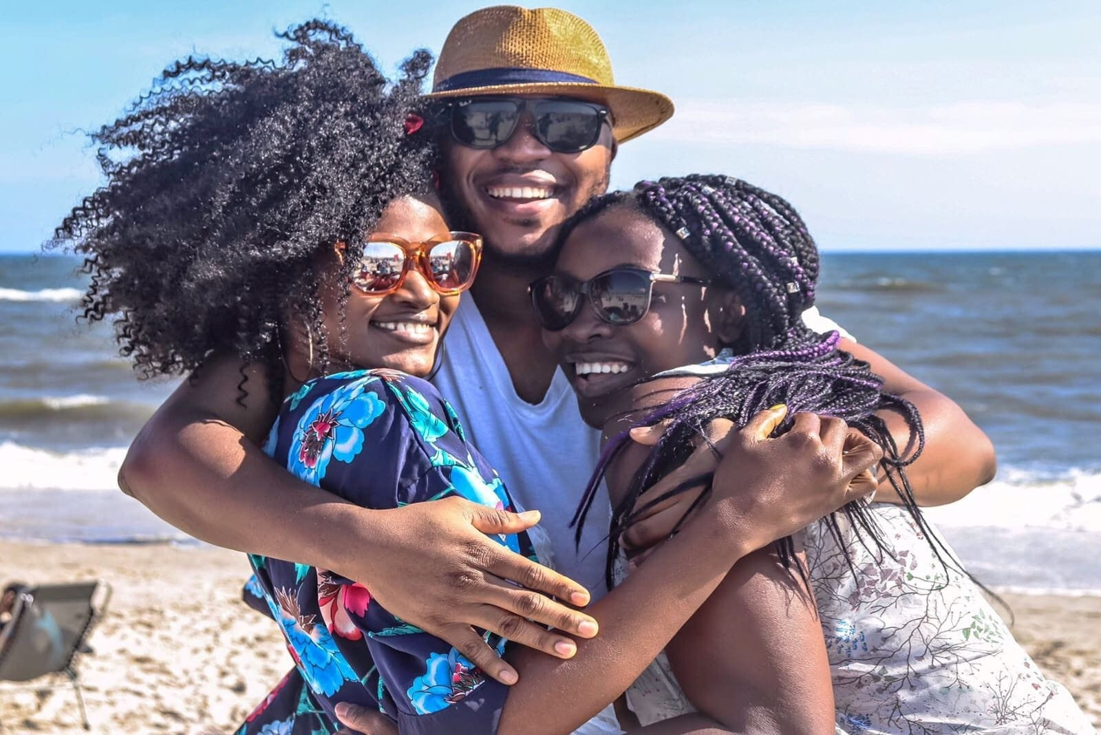 happy man with hat hugging two women