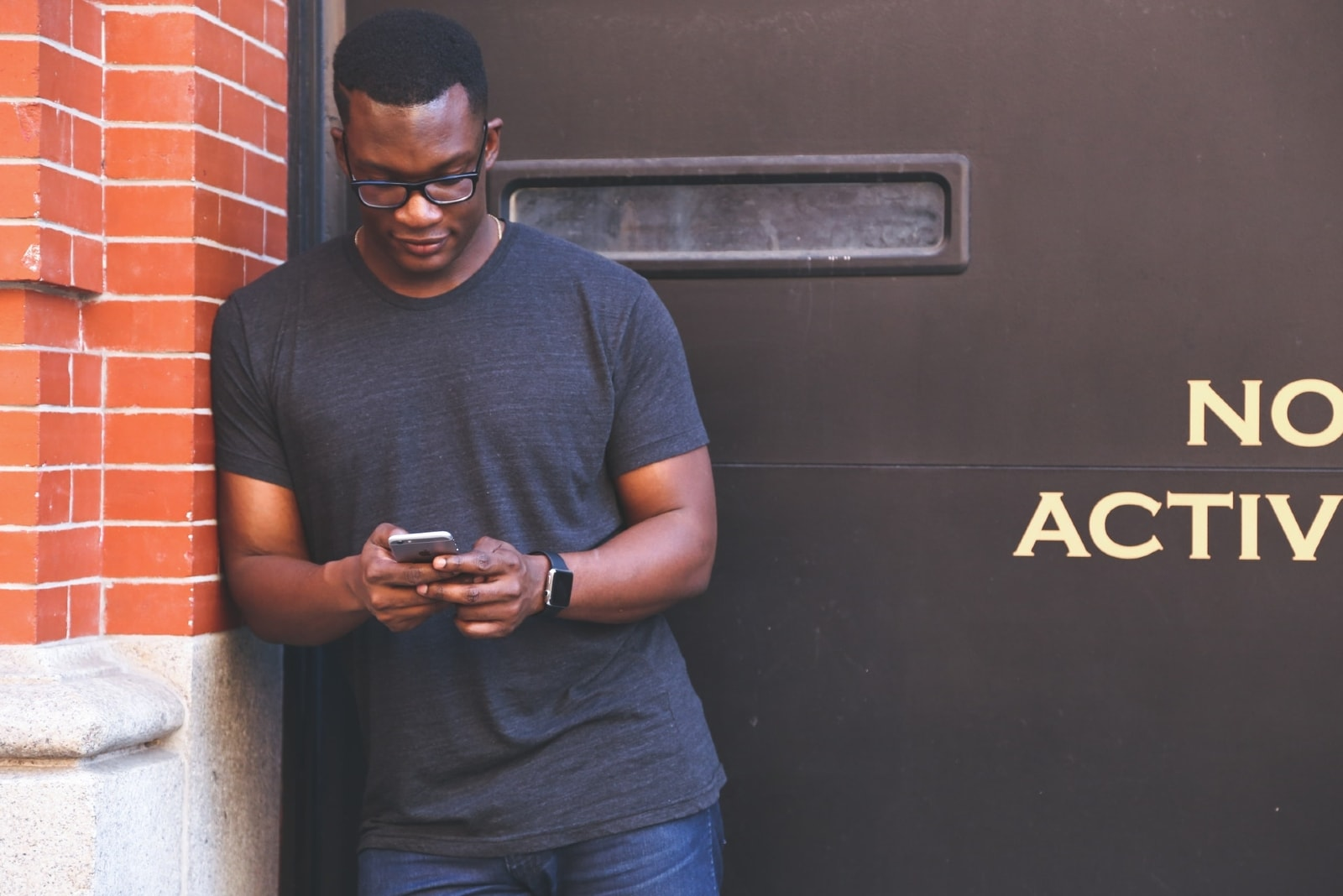 man leaning on brick wall while using smartphone