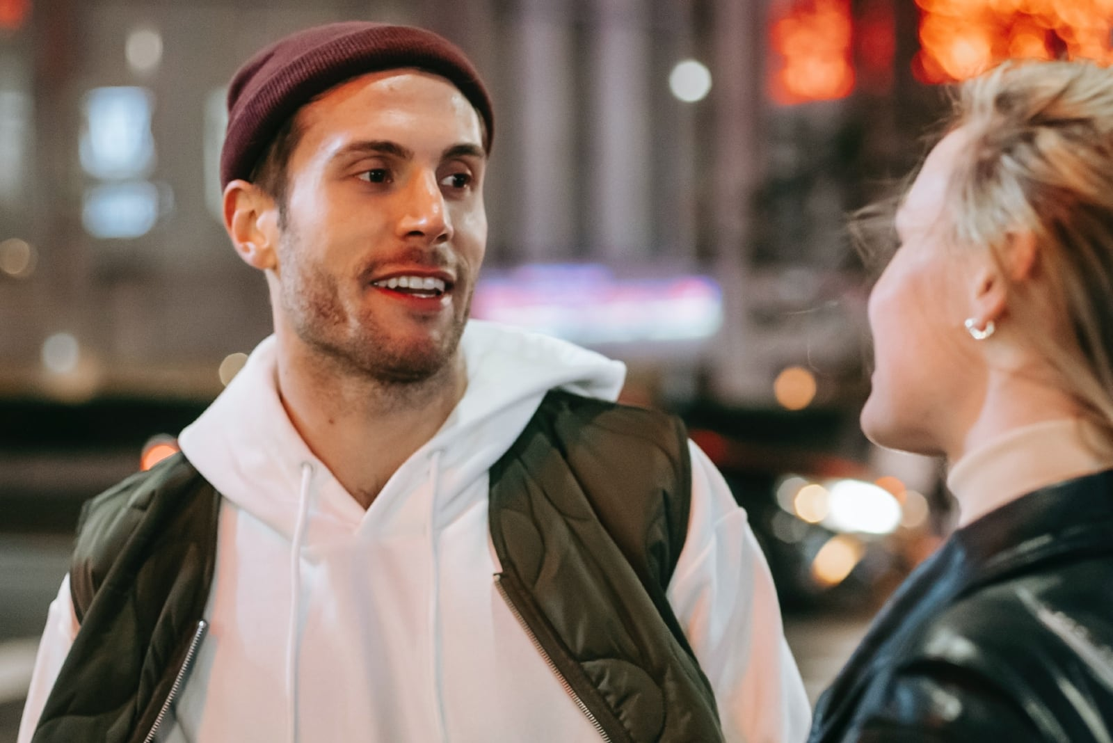 happy man looking at woman while standing on street