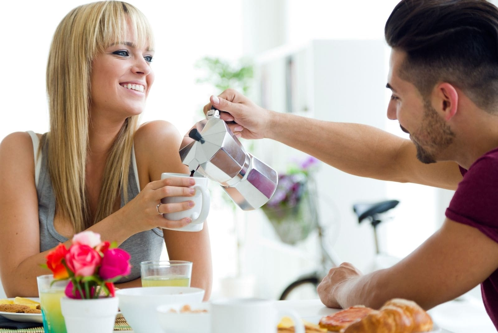 man pouring in coffee in the the cup of the woman during breakfast