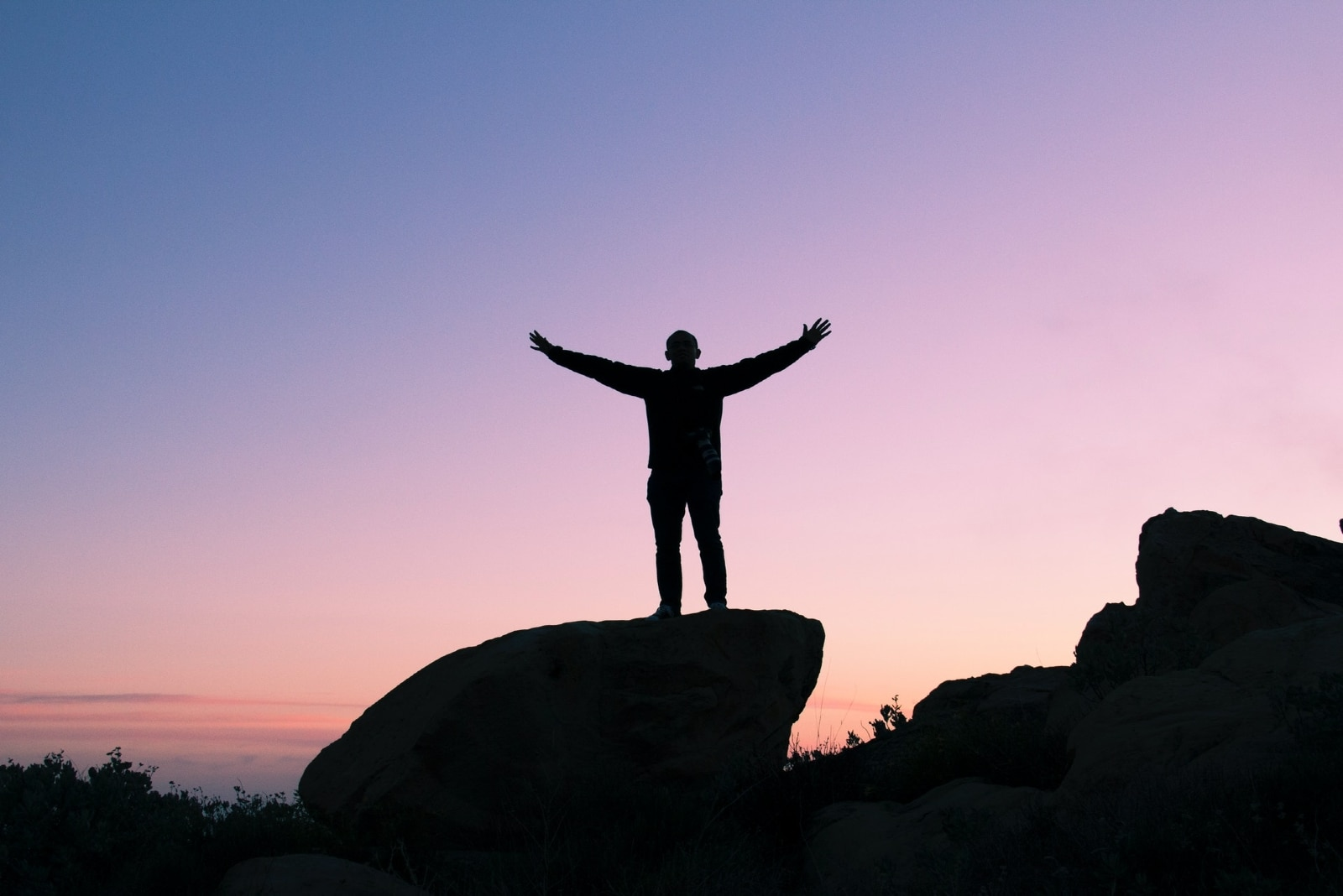 man raising his hands while standing on rock during sunset