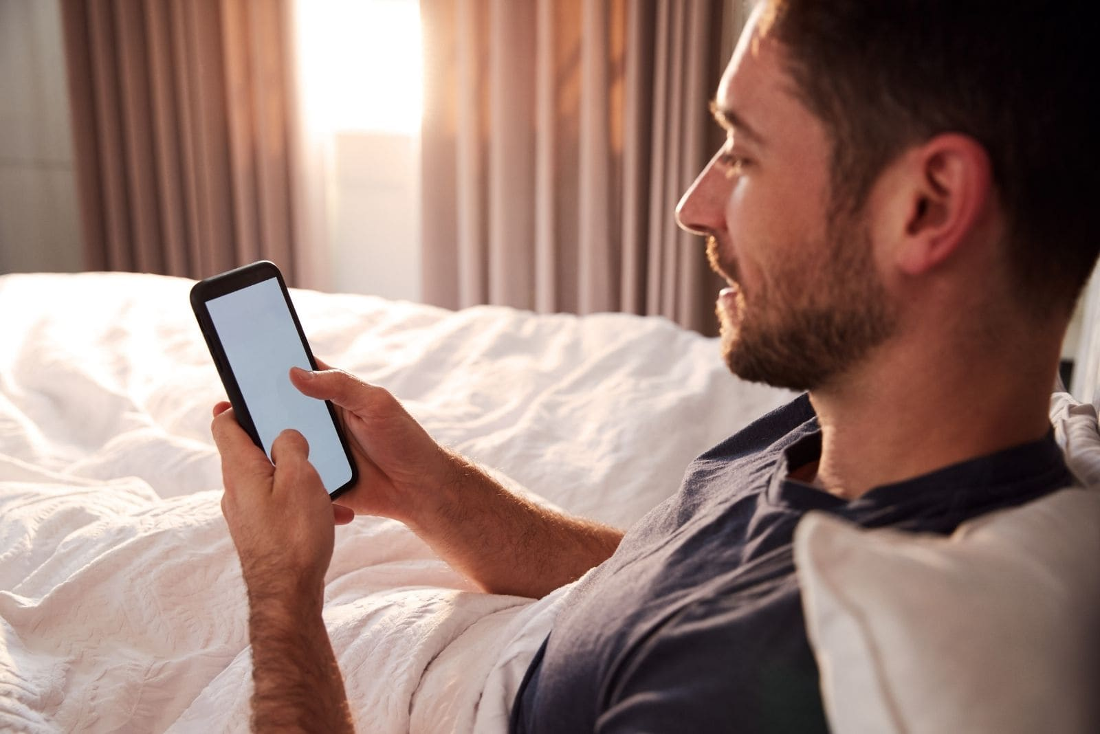 man sitting on bed with his cellphone on sideview inside bedroom