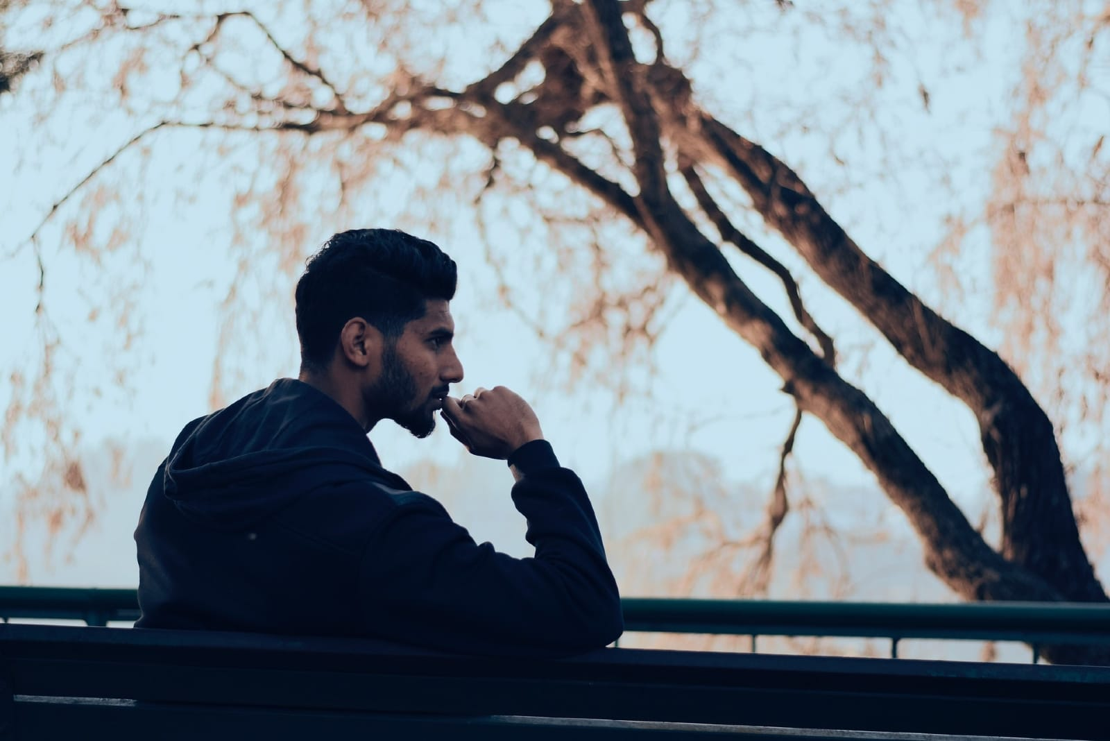 pensive man in black jacket sitting on bench