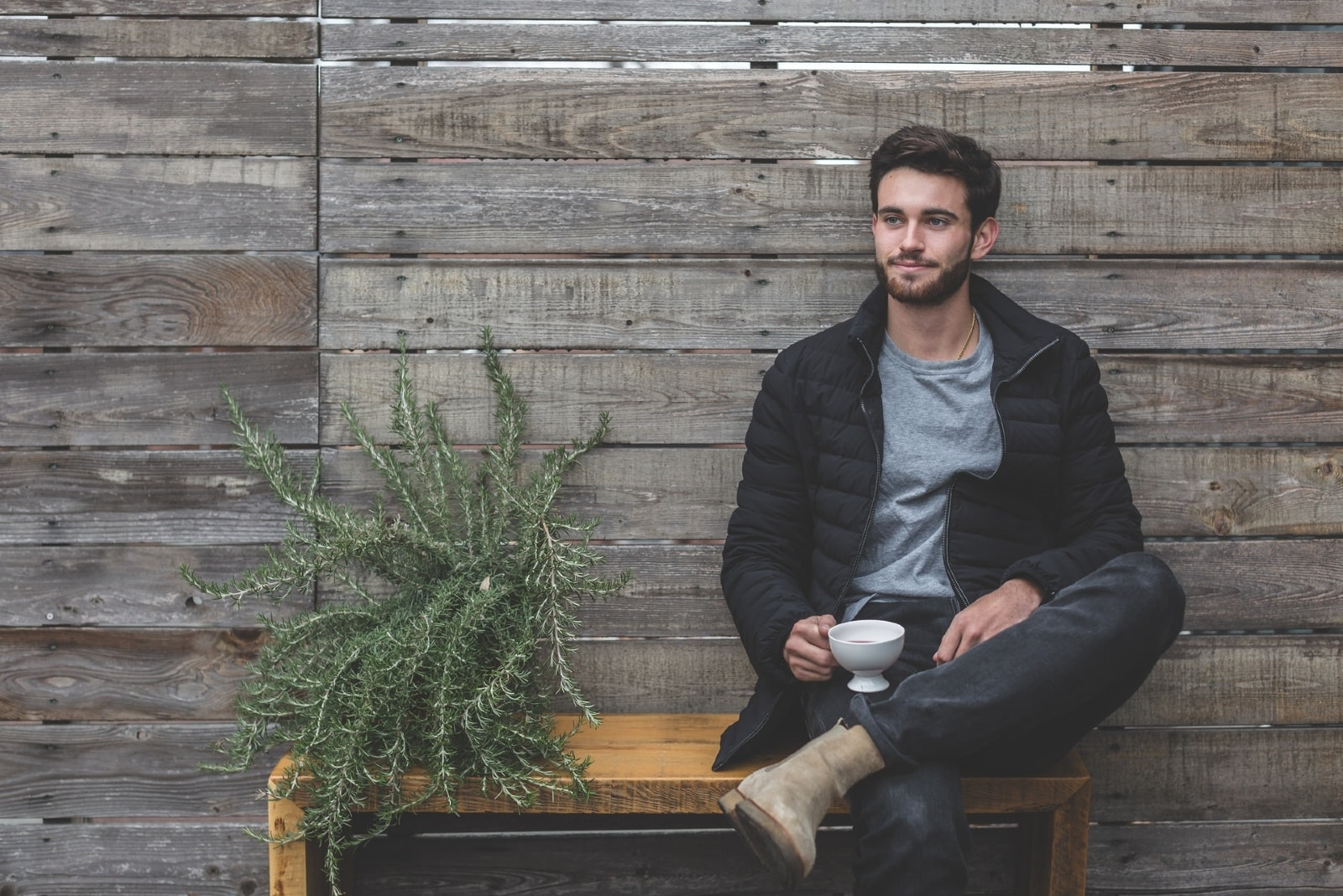 man having coffee while sitting on bench