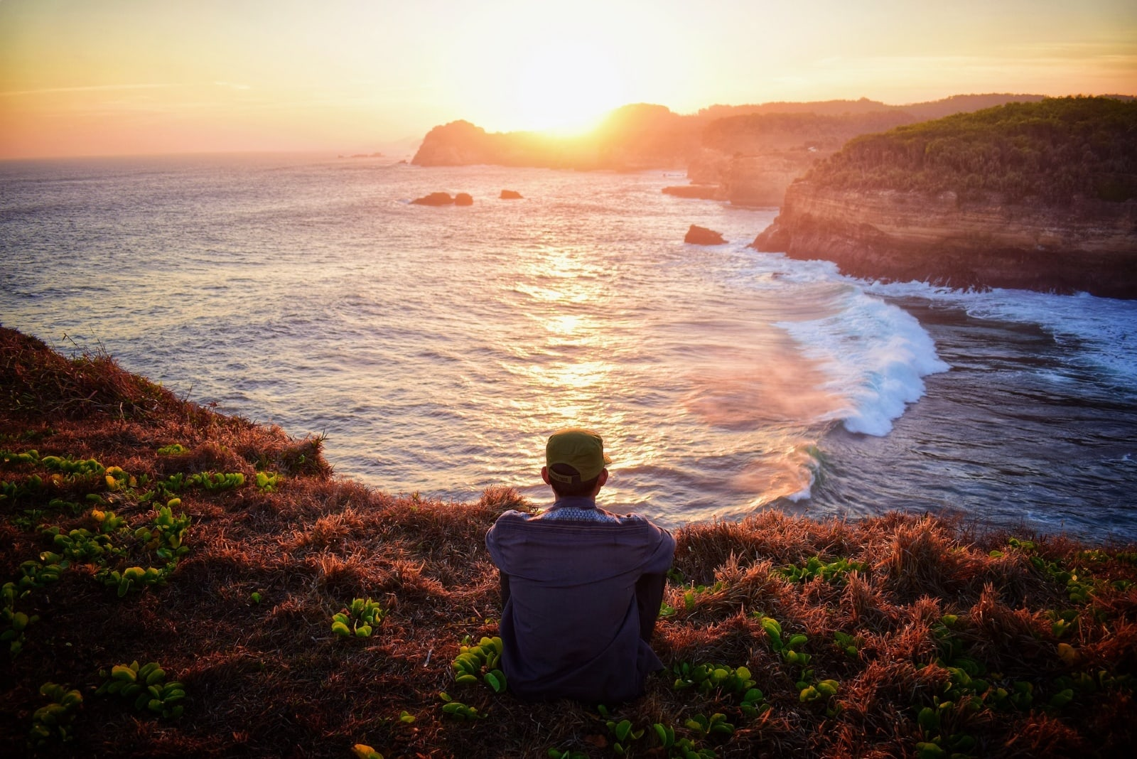 man sitting on grass looking at ocean