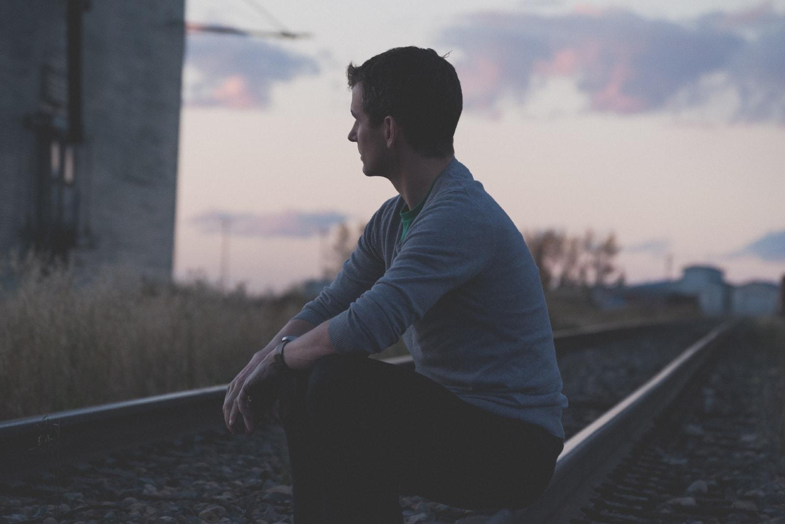 man in gray sweater sitting on railway