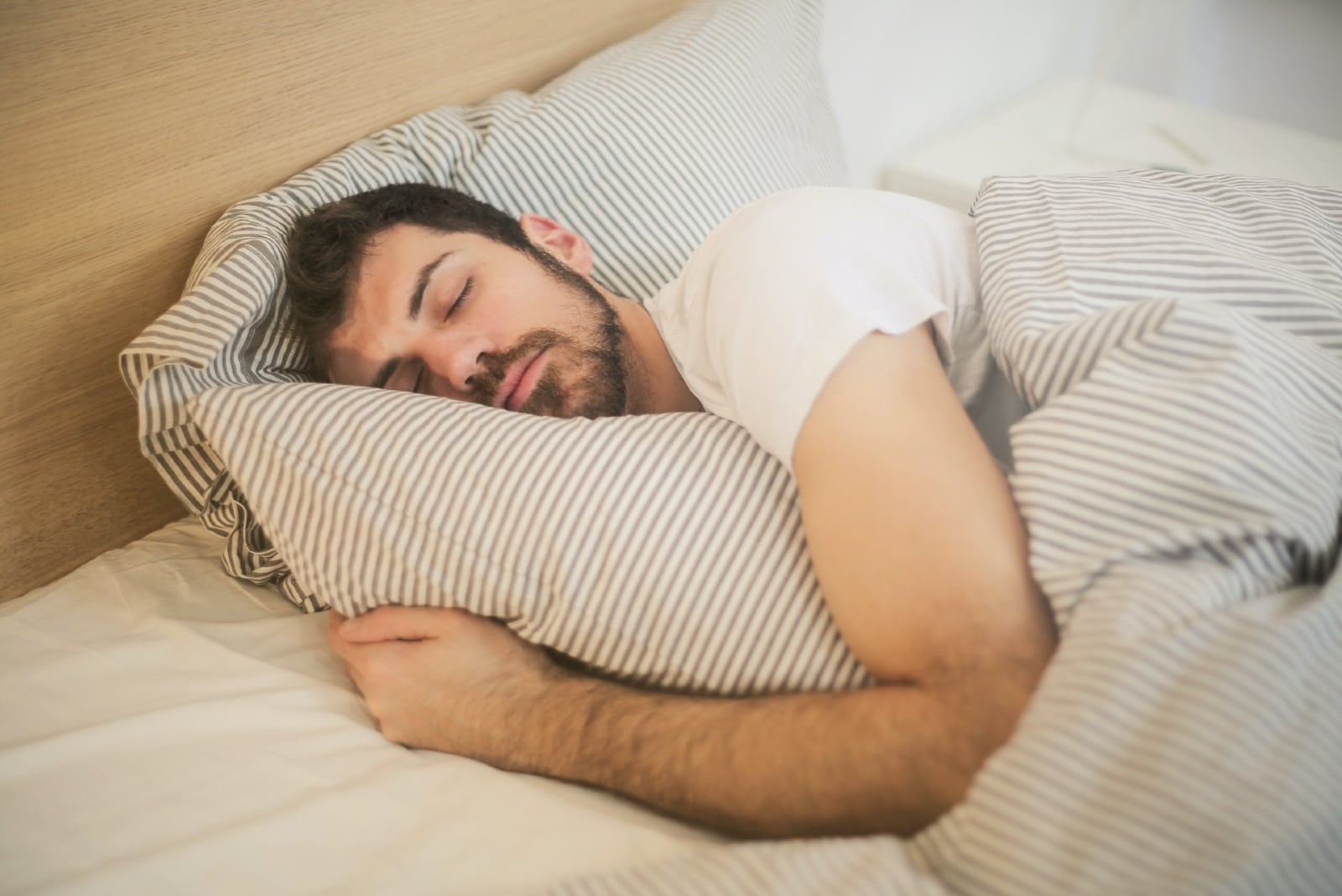 man in white t-shirt sleeping in bed